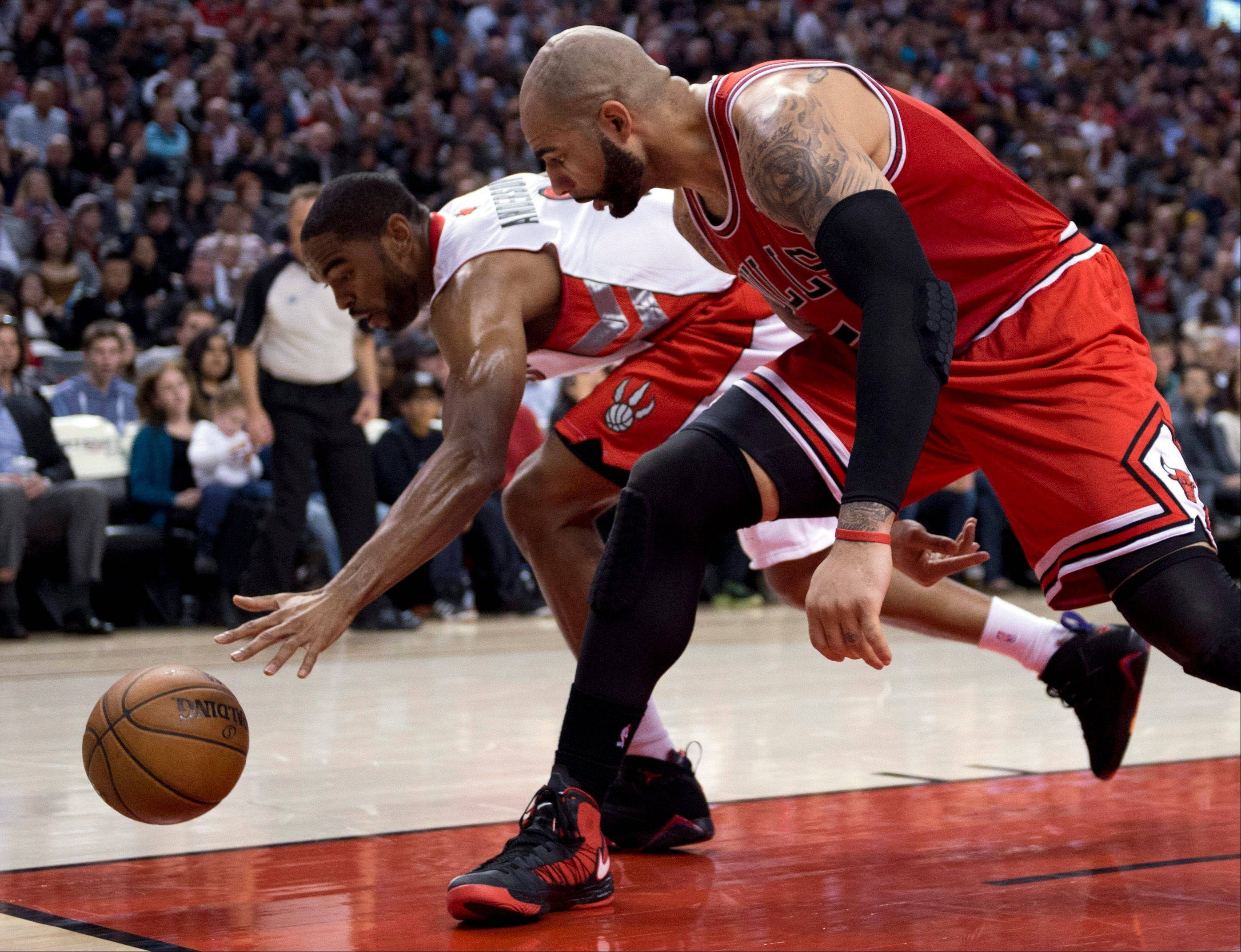 Toronto Raptors forward Alan Anderson and Chicago Bulls forward Carlos Boozer, right, chase down the loose ball during the first half NBA basketball game in Toronto on Friday, April 12, 2013. (AP Photo/The Canadian Press, Frank Gunn)