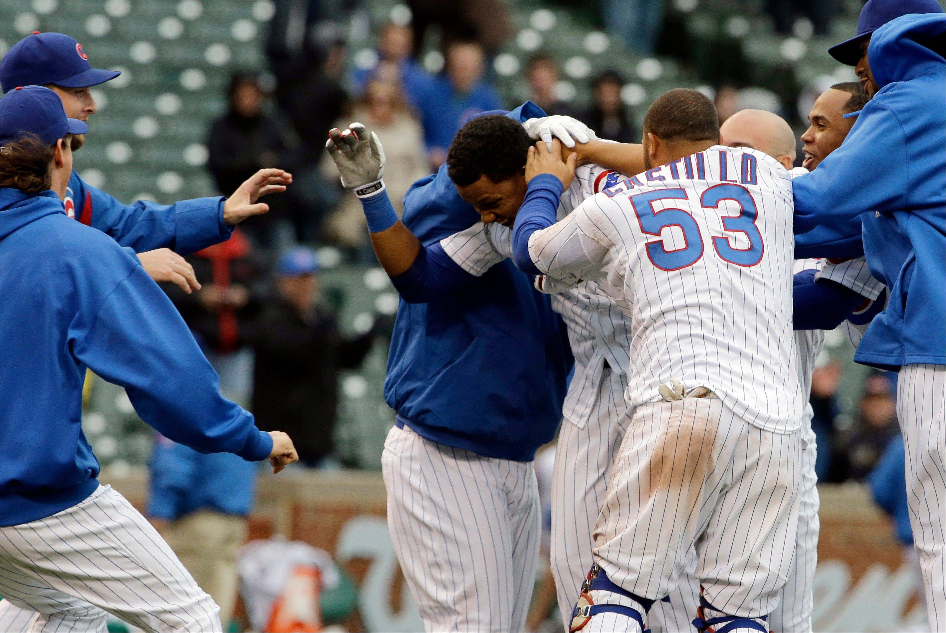 The Cubs� Starlin Castro, center, celebrates with teammates after hitting a game-winning double against the Giants in the ninth inning Friday at Wrigley Field.