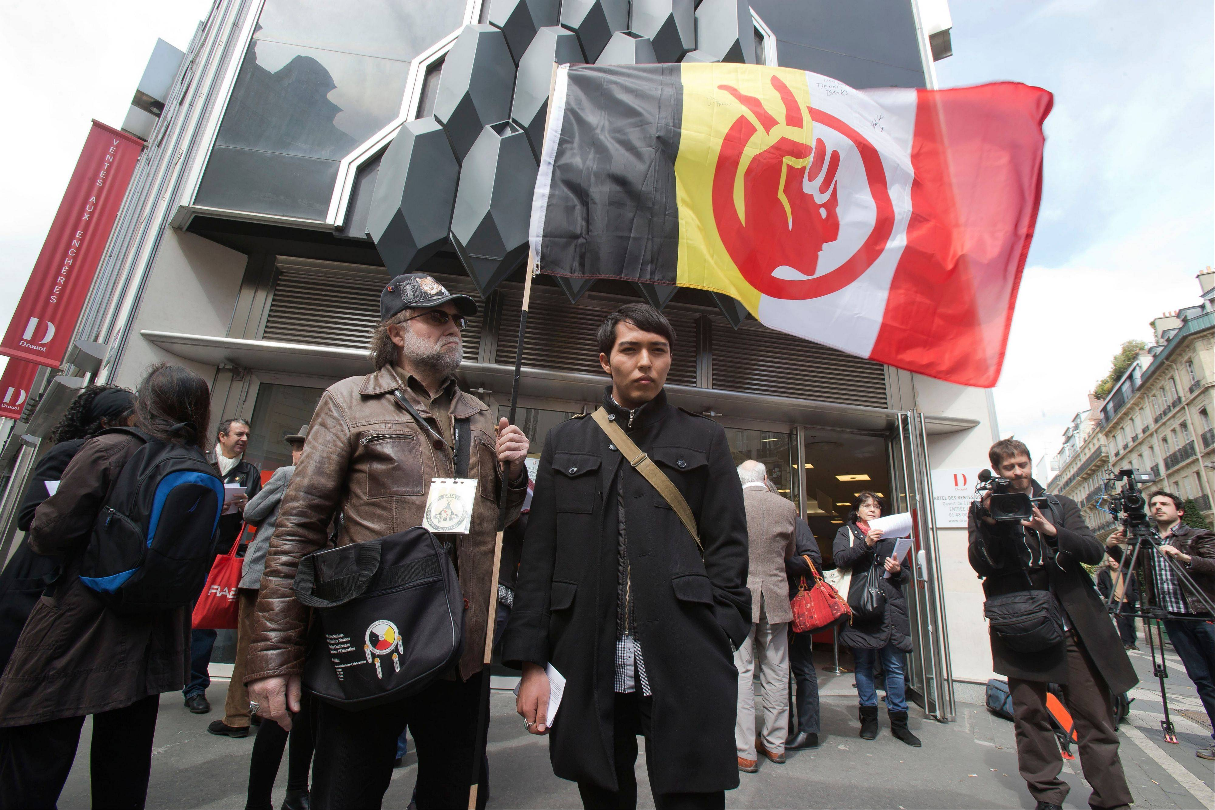 A French supporter of the Indian cause, who refused to give his name, left, holds a flag of the American Indian Movement and an American exchange student, member of the Arizona's Hopi tribe, Bo Lomahquahu, right, stand outside of the Druout's auction house to protest the auction of Native American Hopi tribe masks in Paris, Friday, April 12, 2013. A contested auction of dozens of Native American tribal masks went ahead Friday afternoon following a Paris court ruling, in spite of appeals for a delay by the Hopi tribe, its supporters including actor Robert Redford, and the U.S. government.