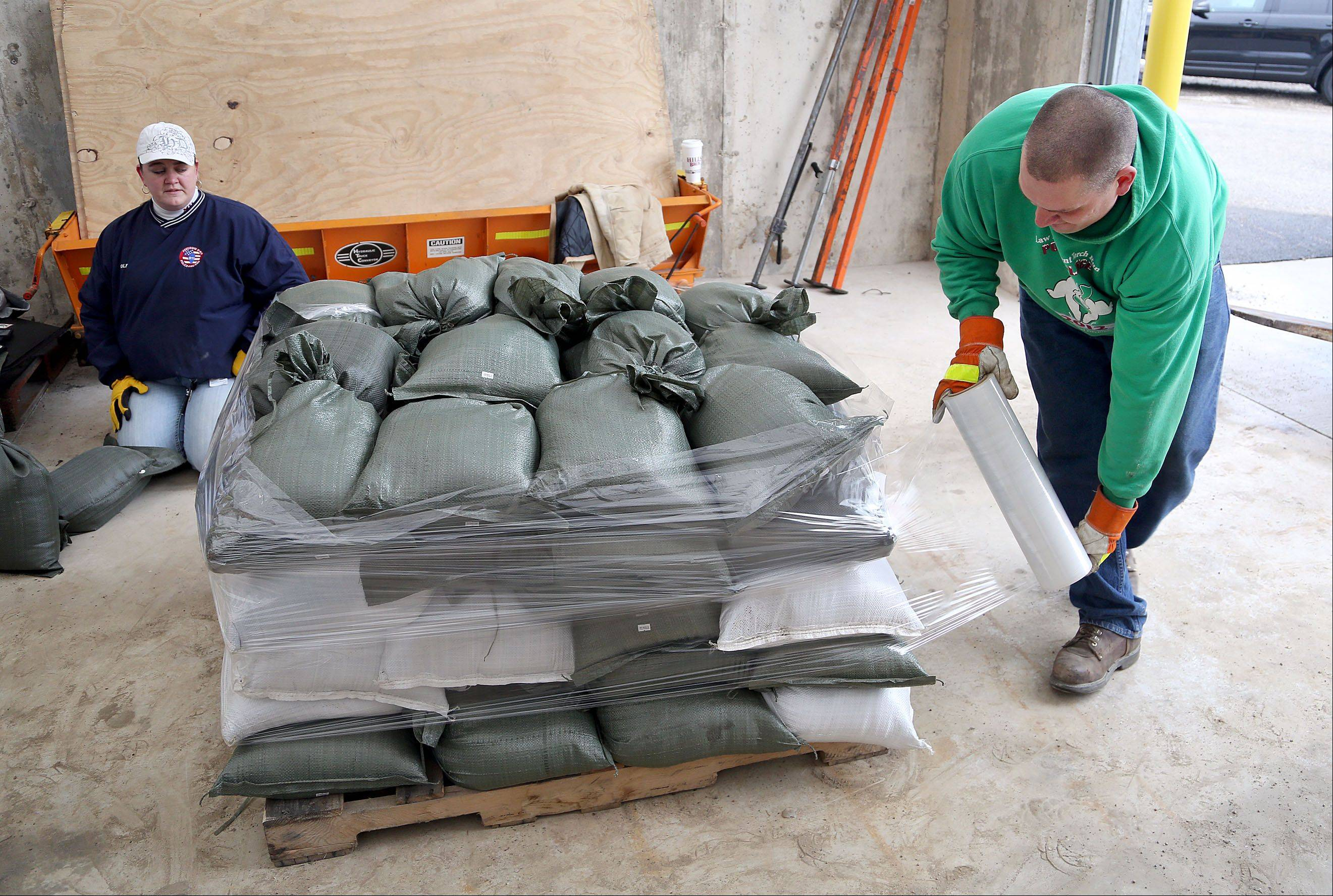 Fox Lake Works Department employee Dana Magness wraps a palate of sand bags at the Fox Lake Works Building Friday morning. The bags will be distributed to areas commonly affected by flooding in the Fox Lake area.