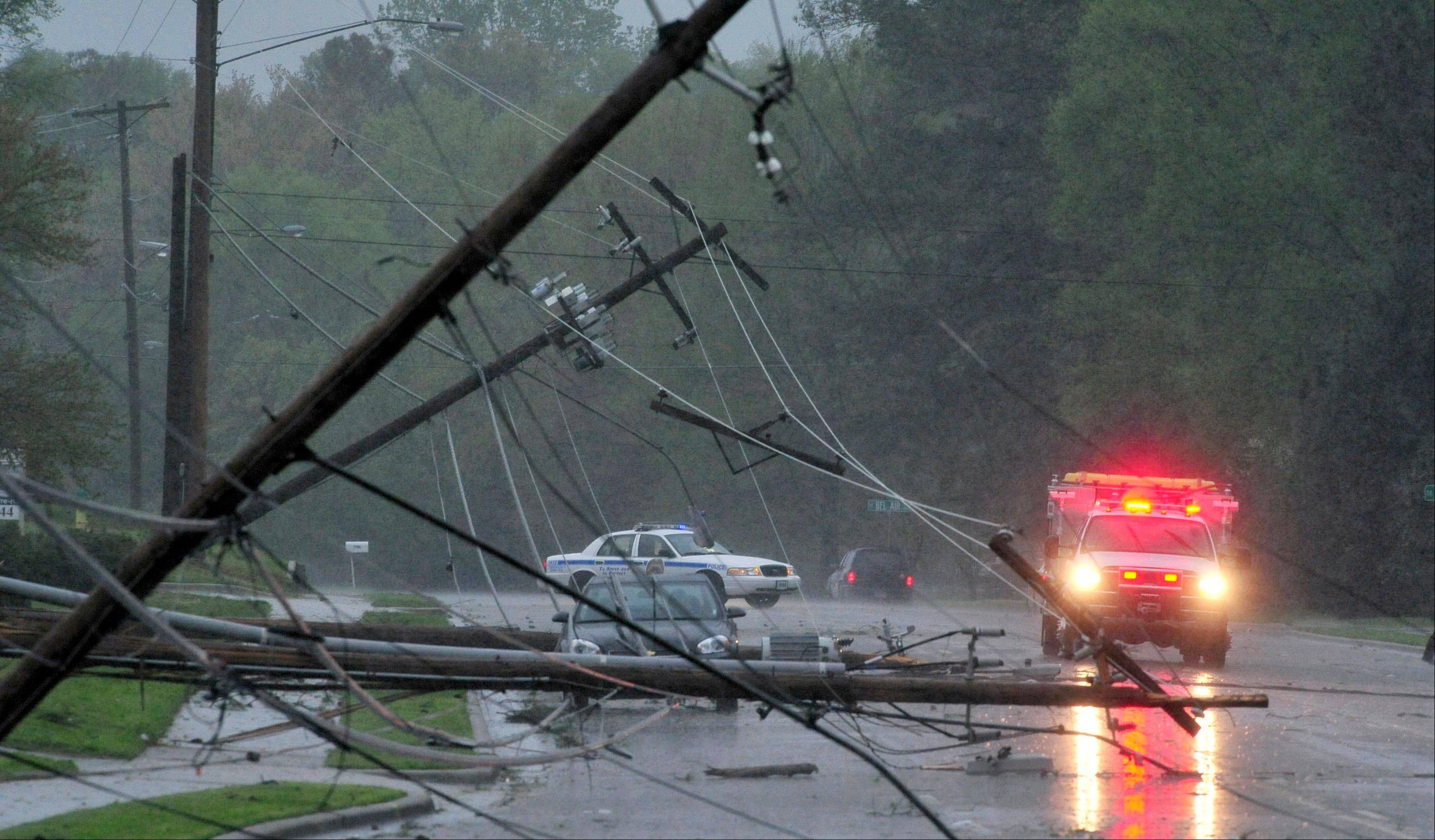A car is trapped under power lines on Whitesburg Drive as strong storms swept through Huntsville, Ala. Thursday, April 11, 2013. A strong spring storm that socked the Midwest with ice and heavy, wet snow made its way east, raking the South with tornadoes Thursday, with three deaths blamed on the rough weather and thousands of people without power.