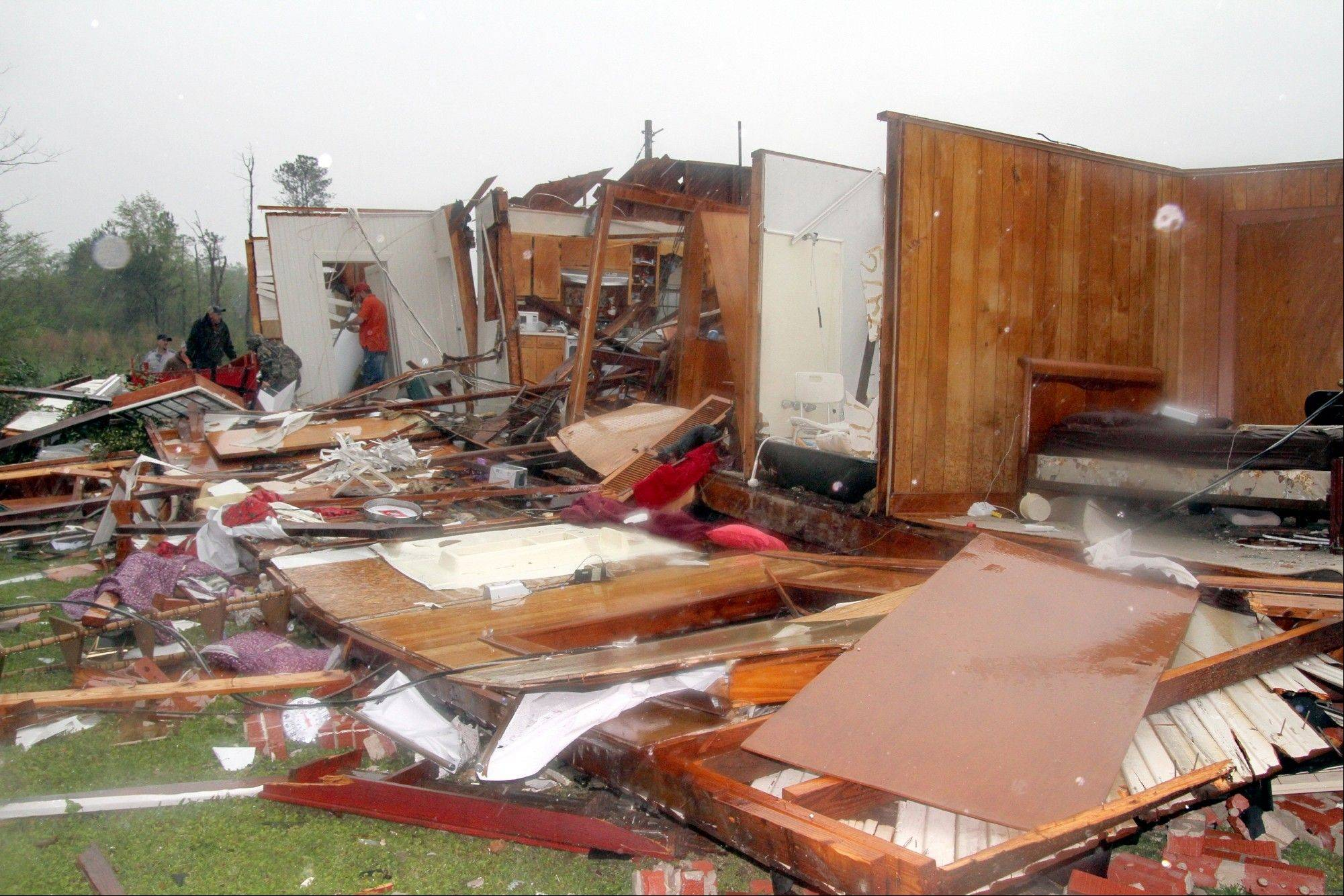 Family members and friends search through Ralph Sciple's home on Highway 397 in Kemper County, Miss., after a tornado ripped through the area Thursday, April 11, 2013. The Sciples were taken to a hospital with minor injuries.