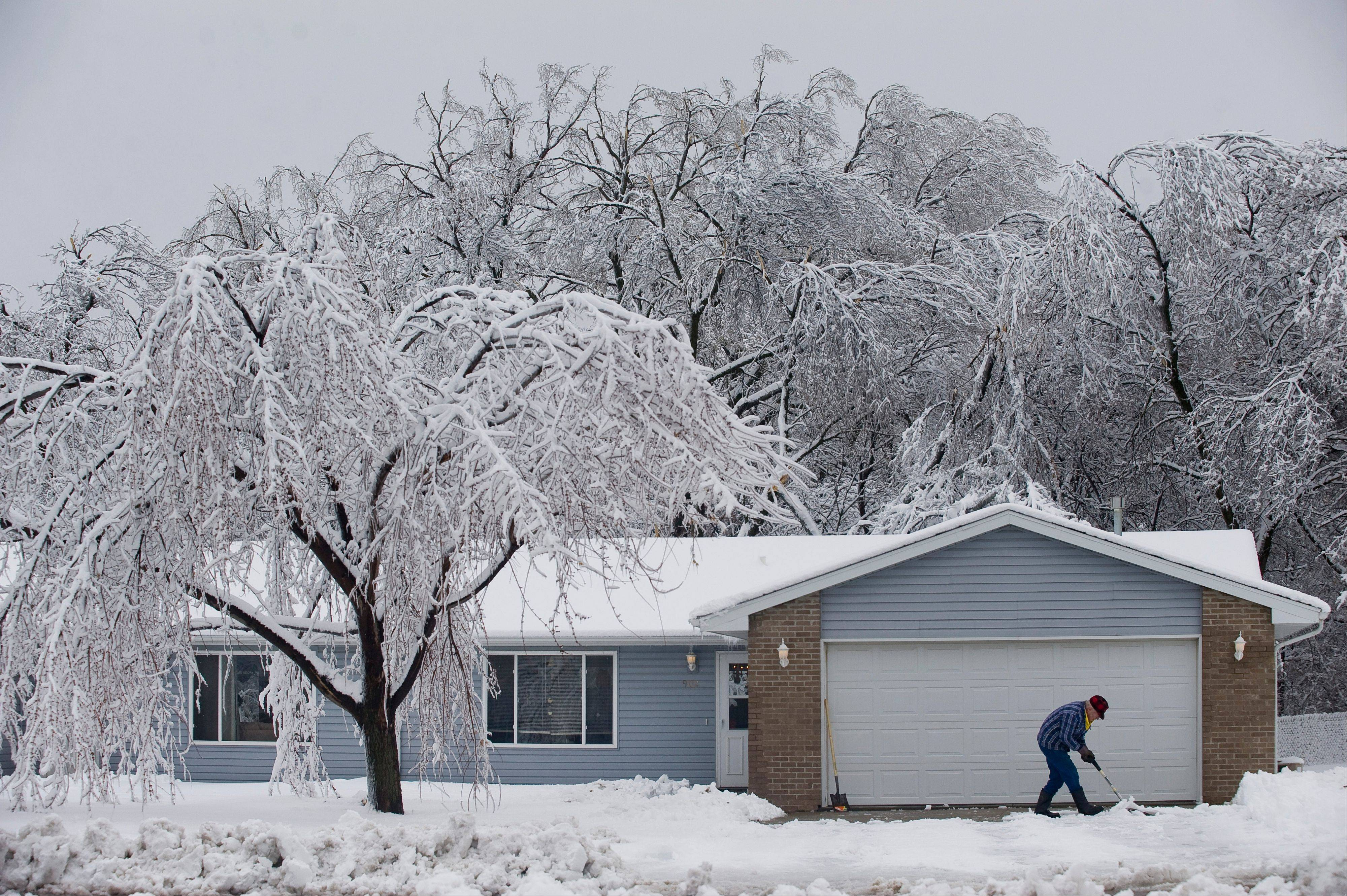 John Deters clears the driveway for his friend, Thursday, April 11, 2013, in Sioux Falls, S.D.