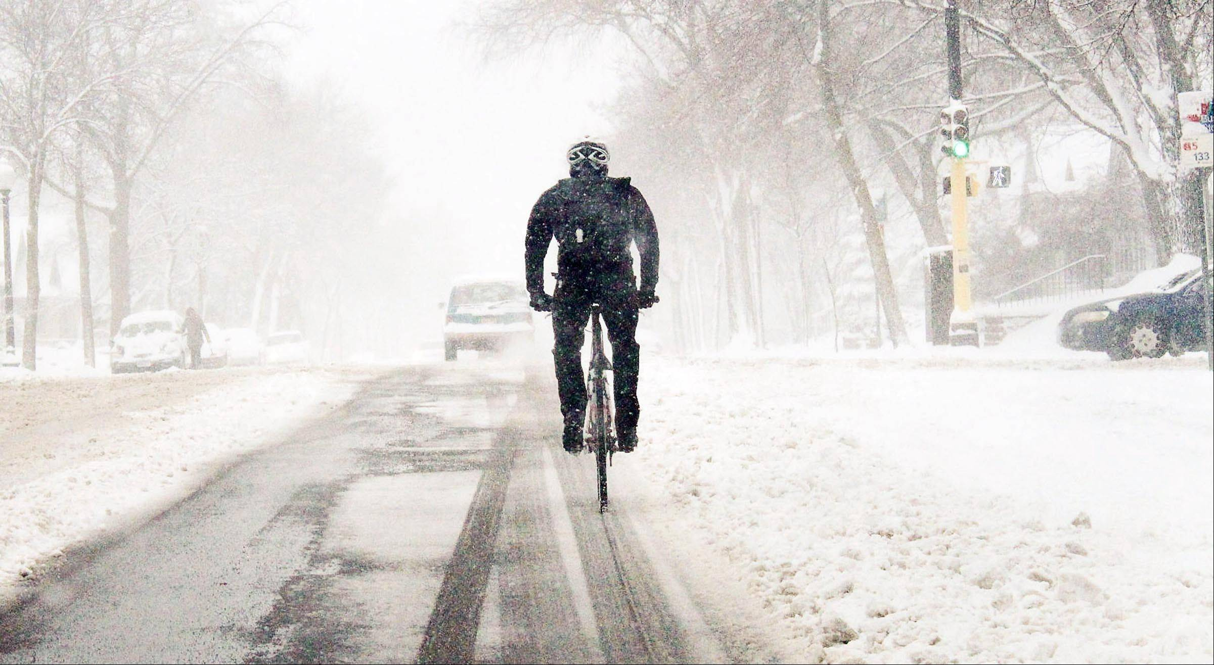 Jeff Frane, 33 tries to bike through the snow on Chicago Avenue in Minneapolis, Minn. on his way to work in Bloomington work on Thursday April 11, 2013. Heavy snow, sleet and gusty winds tested the patience of morning commuters across the southern half of Minnesota on Thursday as residents in the southwest corner of the state dealt with the aftereffects of an ice storm that knocked out power to thousands.