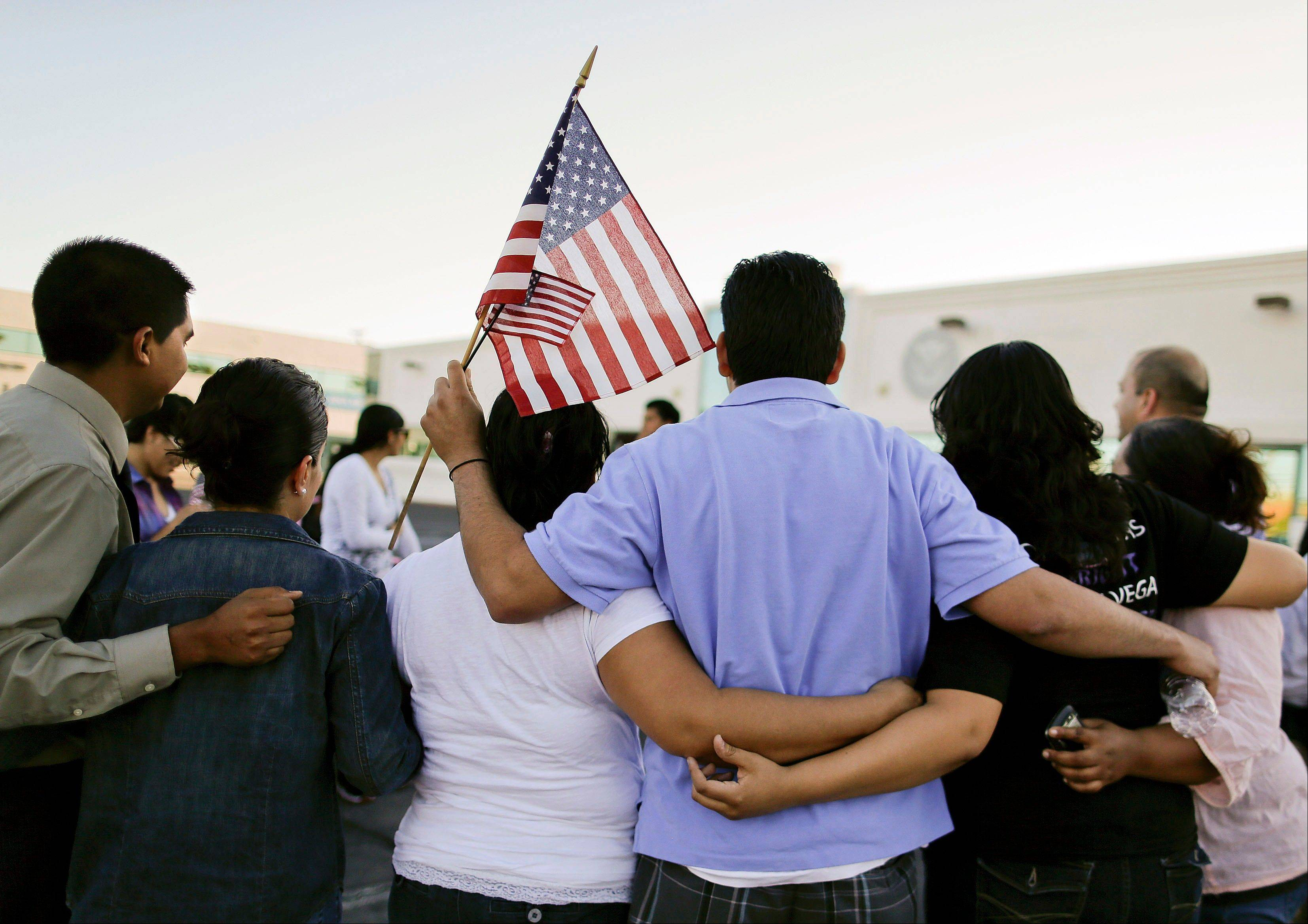 Martin Martinez, center, and his wife, Blanca Martinez, third from left, gather for a photo outside the Immigration and Customs Enforcement offices during an immigration vigil, Wednesday, in Las Vegas.