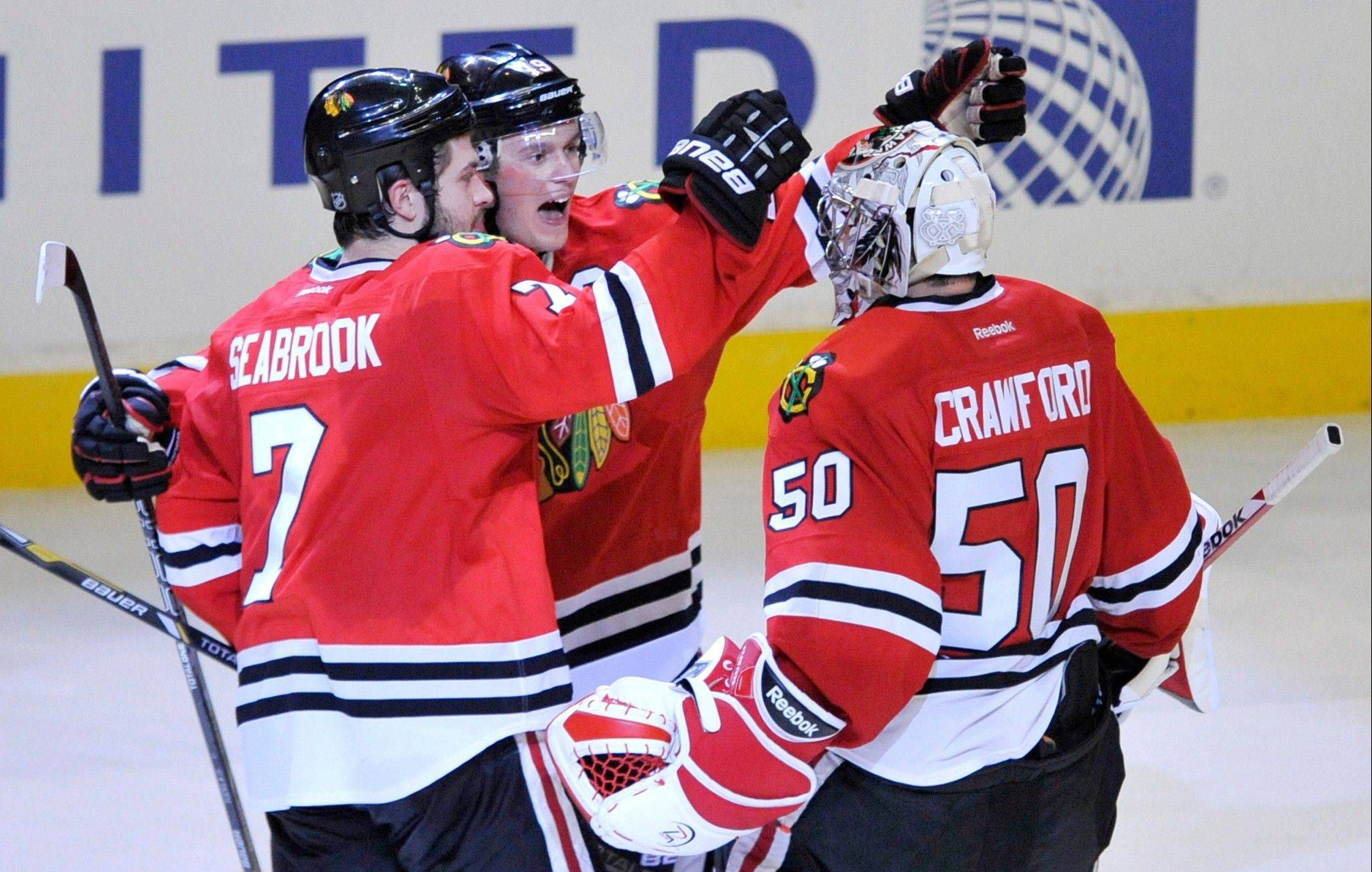Goalie Corey Crawford celebrates with Brent Seabrook and Jonathan Toews after the Blackhawks rallied to beat the Red Wings in a shootout Friday night at the United Center.