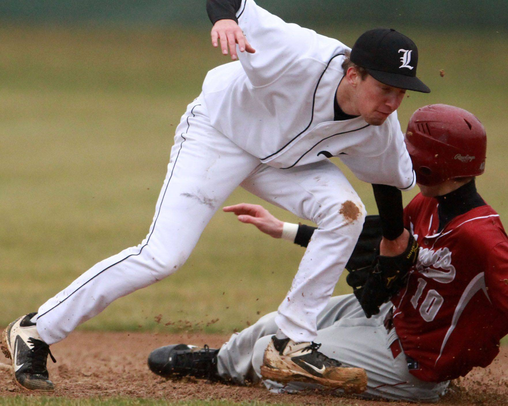 Antioch's Mitch Everett slides into second base as Libertyville shortstop Jimmy Govern just misses the tag; Everett was sent back to first after an interference call at Libertyville on Friday.