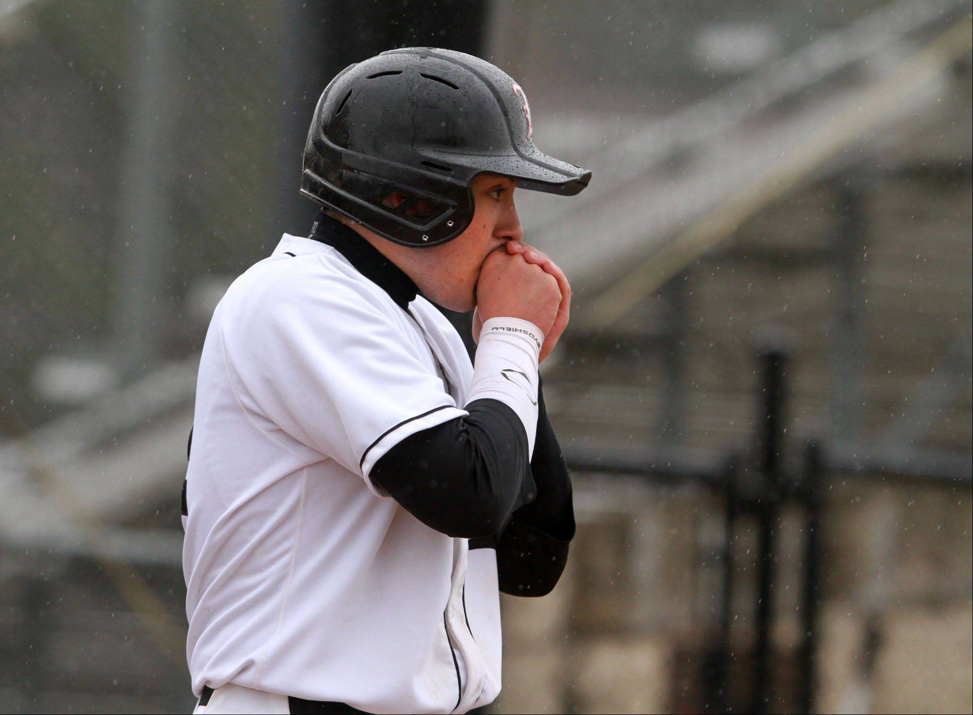 Libertyville's Noah Greenberg warms his hands after batting against Antioch's David Meade at Libertyville on Friday.