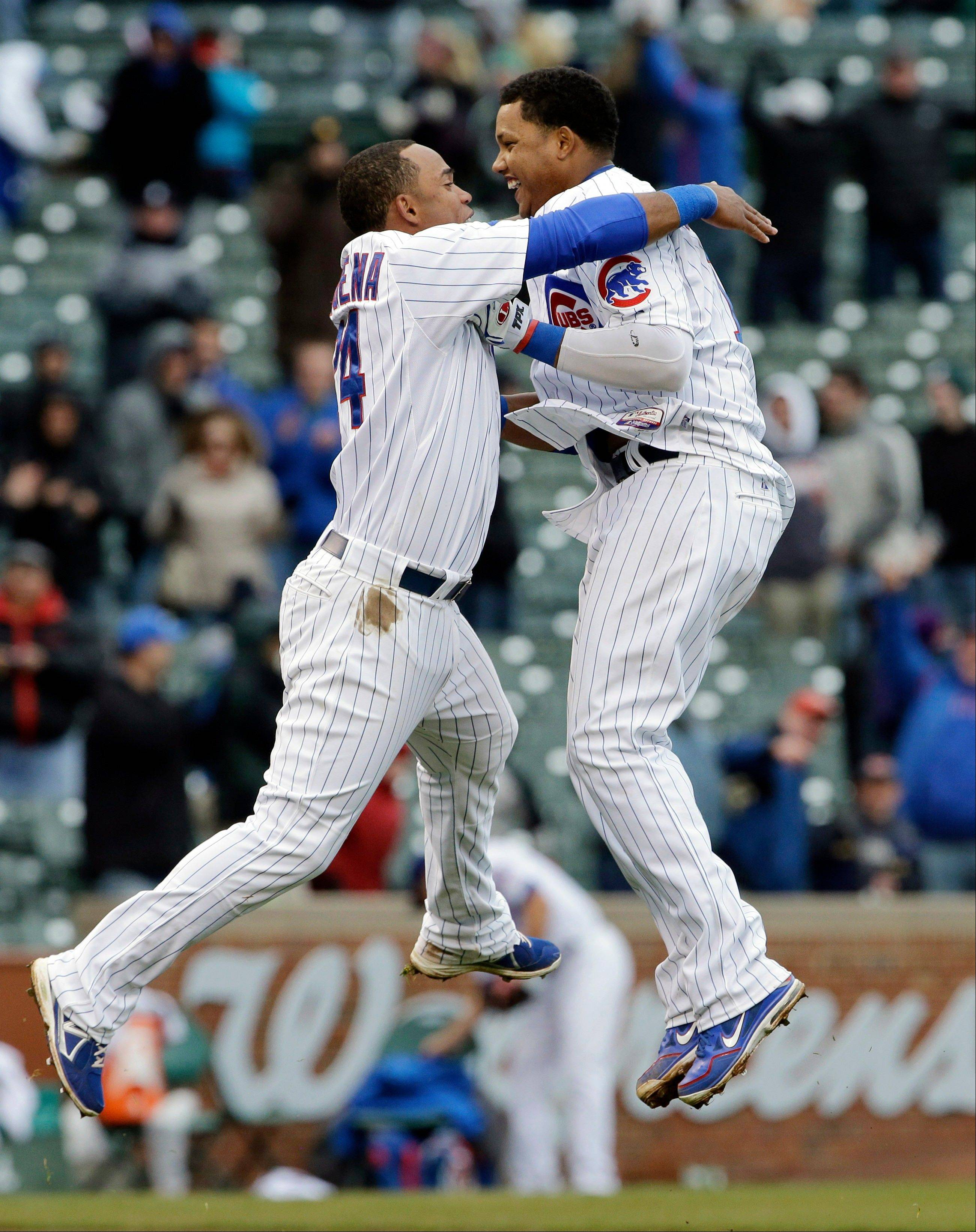 Chicago Cubs' Starlin Castro, right, celebrates with teammate Luis Valbuena after hitting a game-winning double against the San Francisco Giants during the ninth inning of a baseball game in Chicago, Friday, April 12, 2013. The Cubs won 4-3.