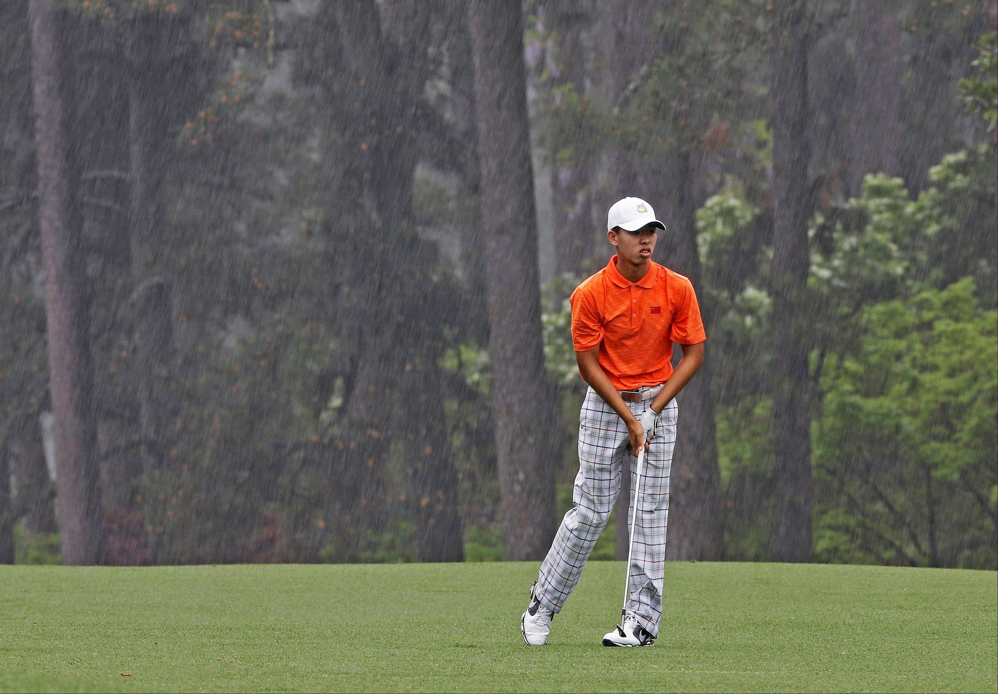 Amateur Guan Tianlang, of China, watches his ball after hitting in the rain on the eighth fairway during the second round of the Masters golf tournament Friday, April 12, 2013, in Augusta, Ga.