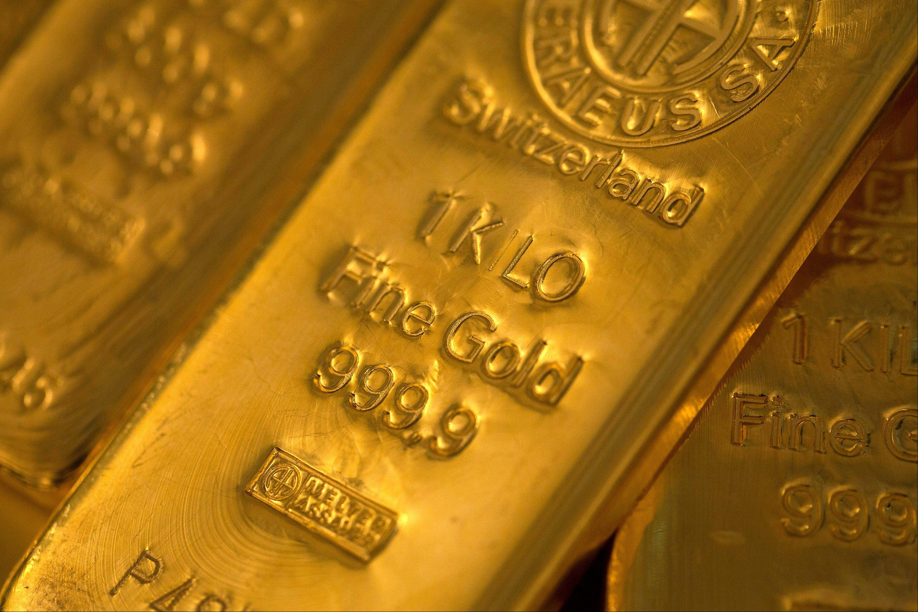Two one kilogram gold bars sit with a 500 gram gold bar at London bullion dealers Gold Investments Ltd. in this file photograph.