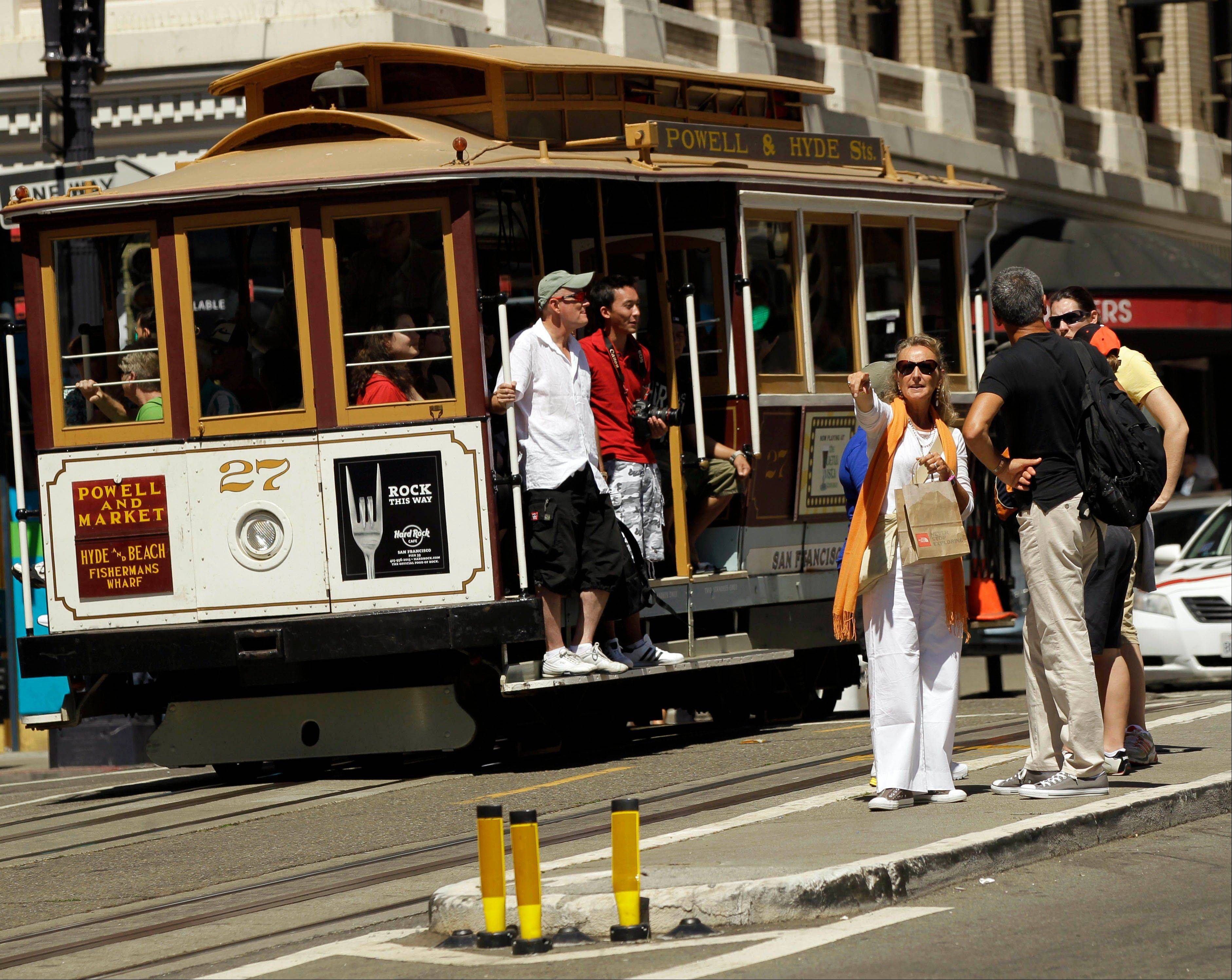 Visitors wait to board a cable car in San Francisco's Union Square.