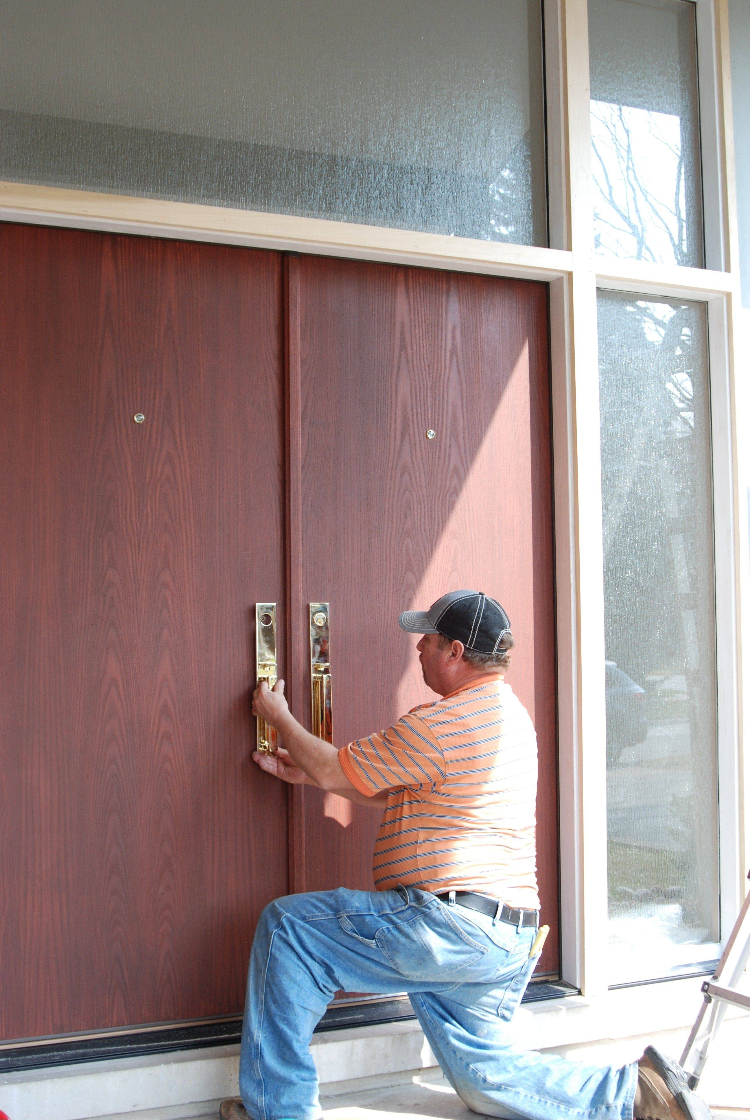 A John Tobin Millwork installer finishes up the hardware on a newly installed door at a home in Park Ridge.