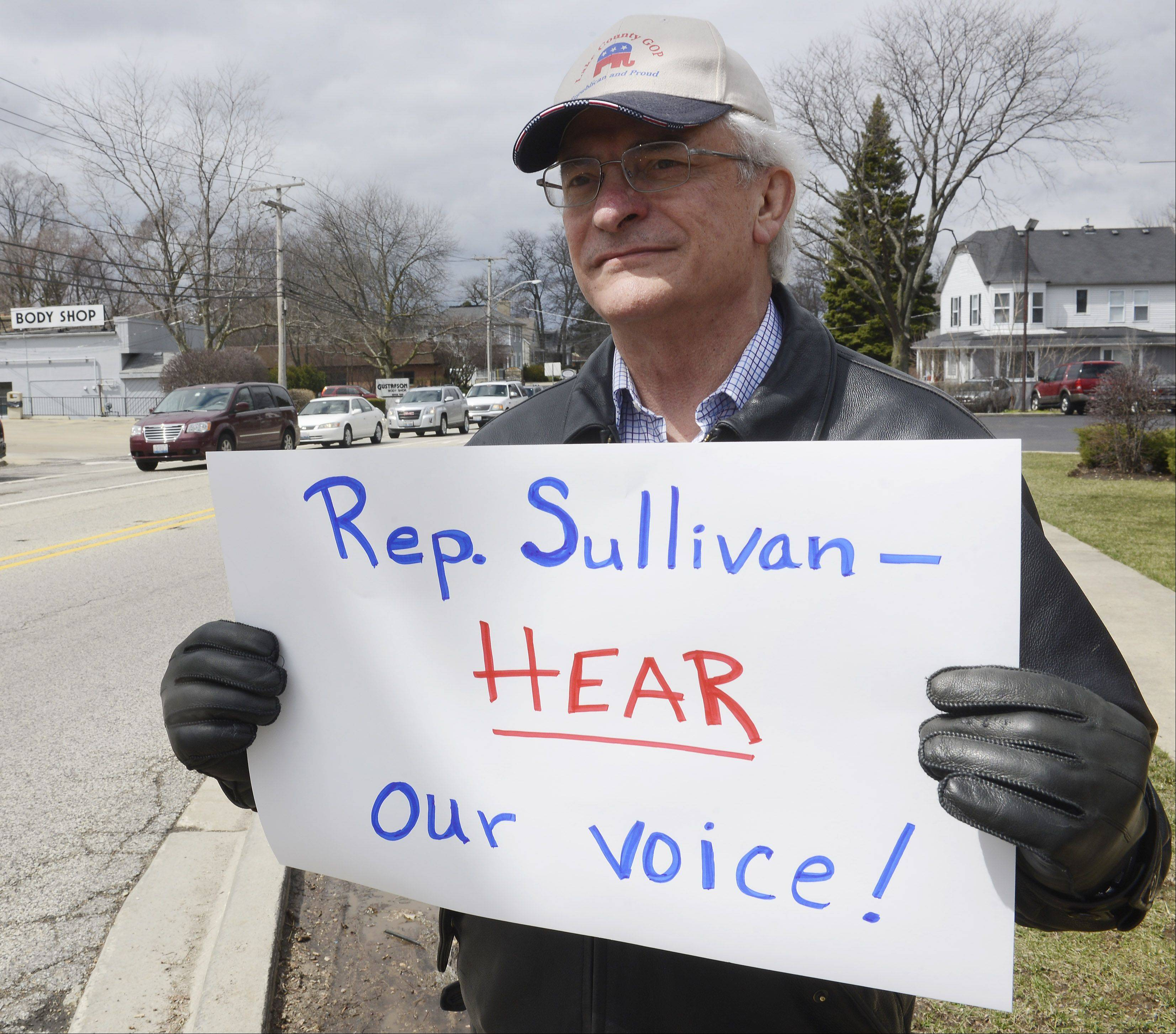 Don Castella of Lincolnshire holds his sign as opponents of gay marriage protest Saturday outside state Rep. Ed Sullivan Jr.'s office in Mundelein.