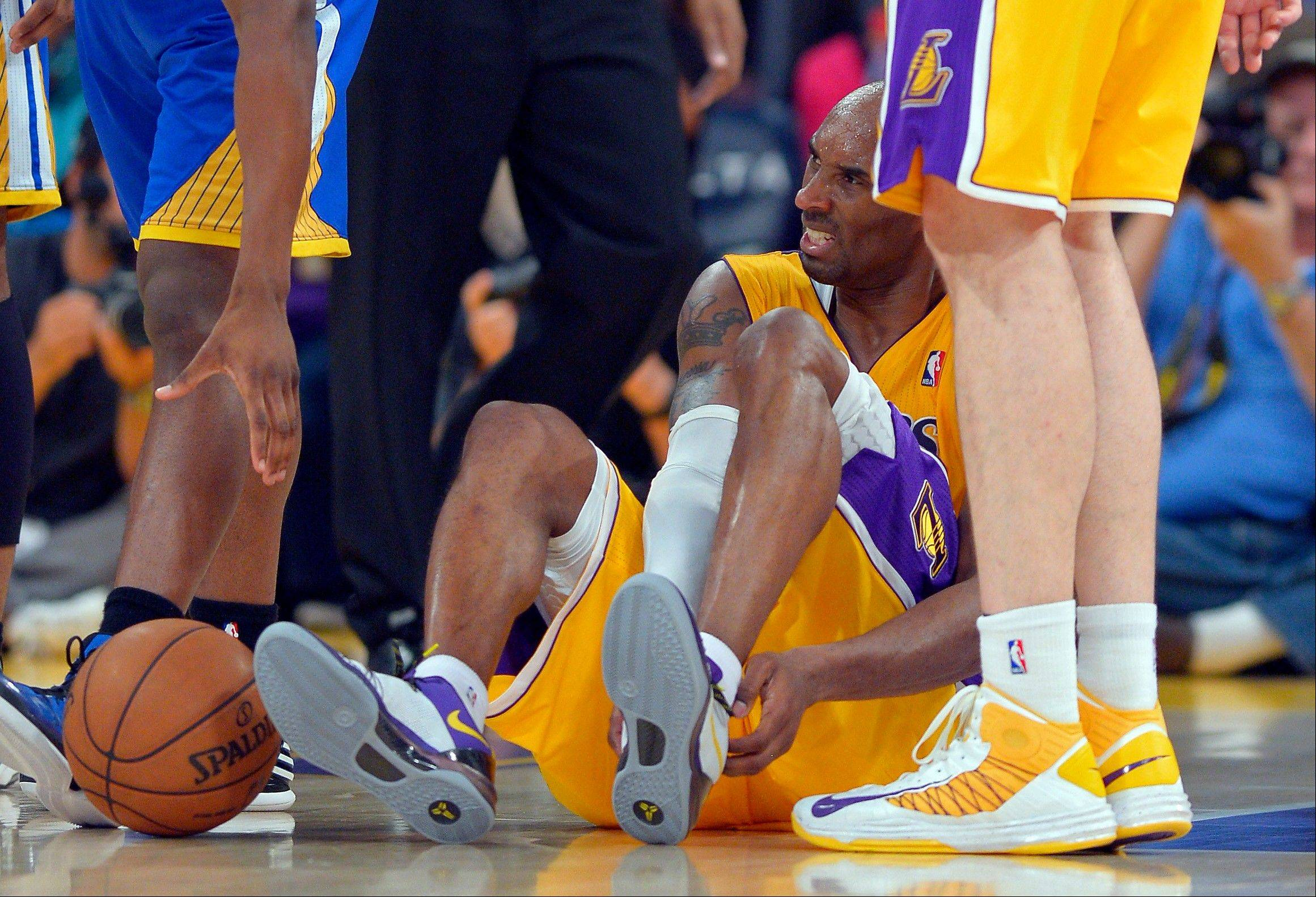 Kobe Bryant grimaces after rupturing his Achilles� tendon Friday. Bryant will be out 6-9 months.