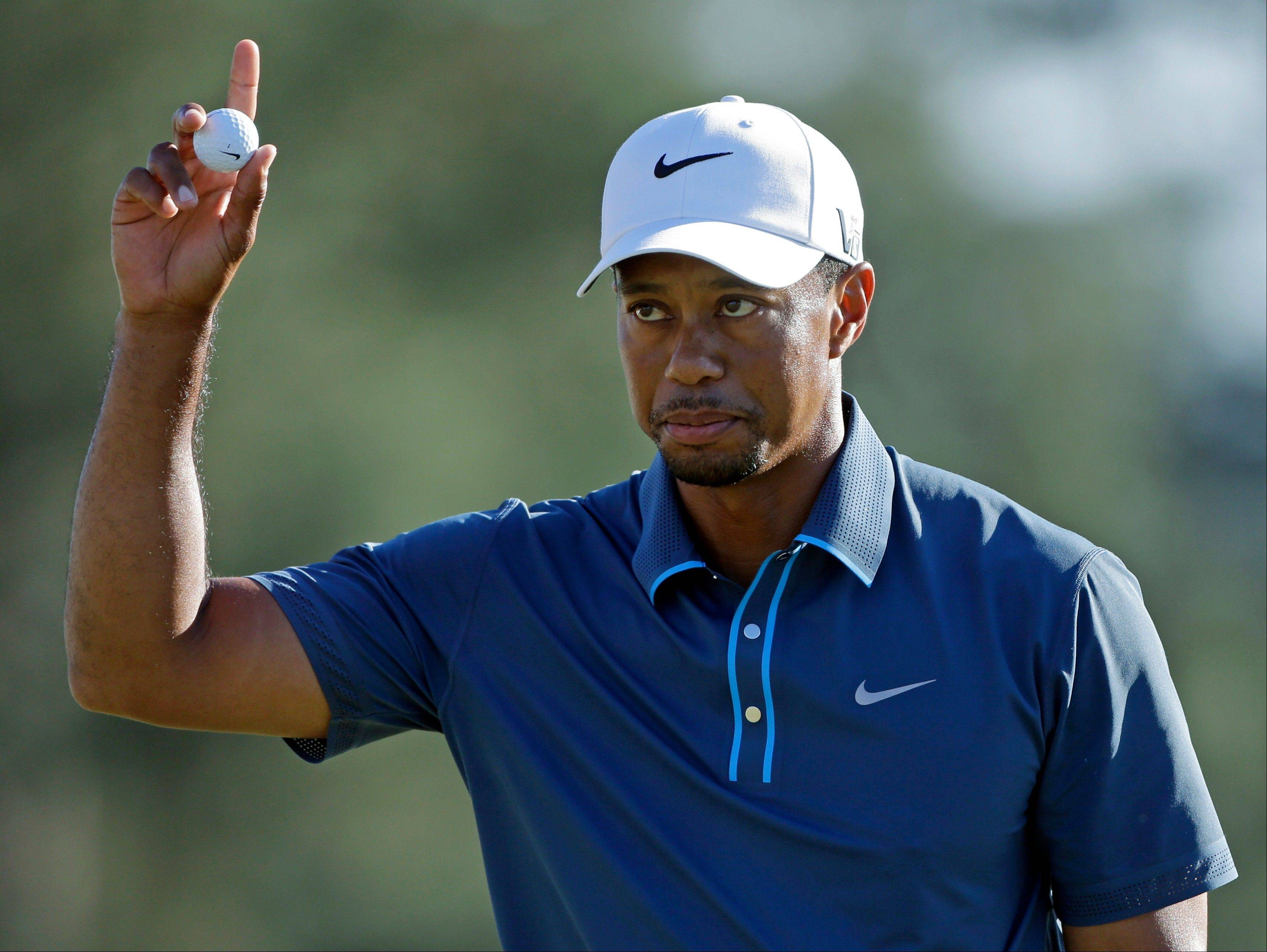 Tiger Woods holds up his ball after putting out on the 18th hole during the third round of the Masters golf tournament Saturday, April 13, 2013, in Augusta, Ga.