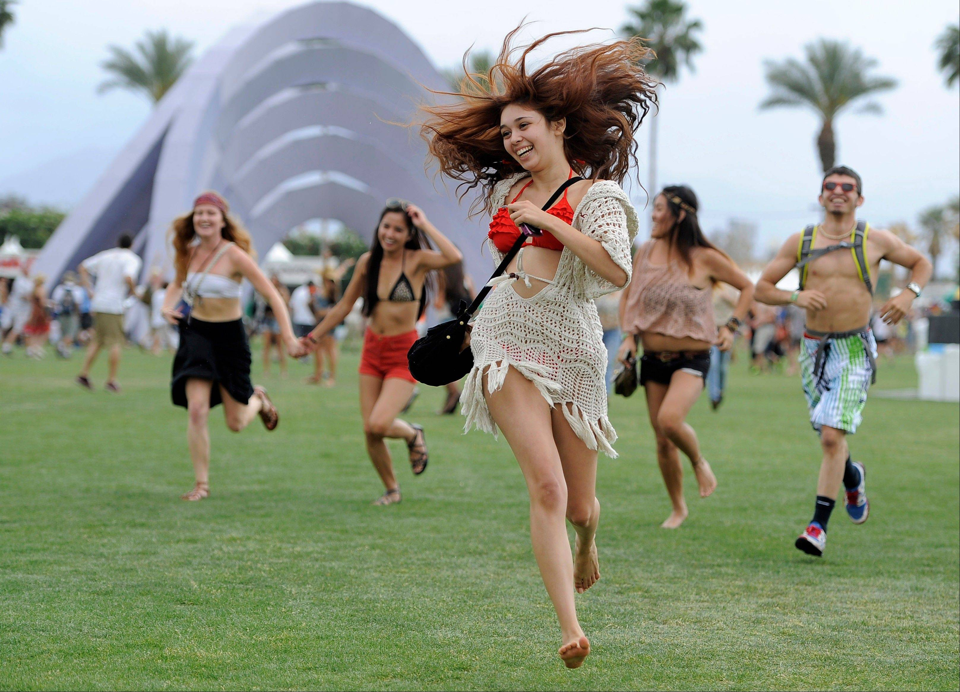 Festival goers run toward the main stage to catch the beginning of Kendrick Lamar's set during the first weekend of the 2012 Coachella Valley Music and Arts Festival in Indio, Calif.