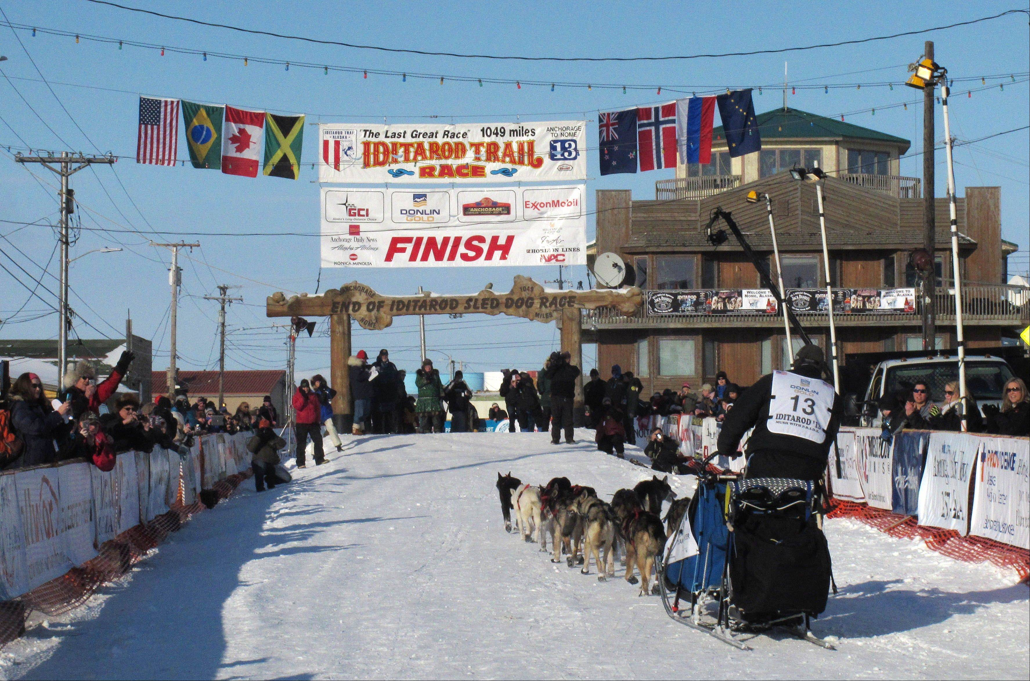 Residents greet Kotzebue musher John Baker as he nears the finish line in Nome, Alaska. If you want to see mushers cross the finish line at the world's most famous sled dog race in March 2014, better make your reservations soon.