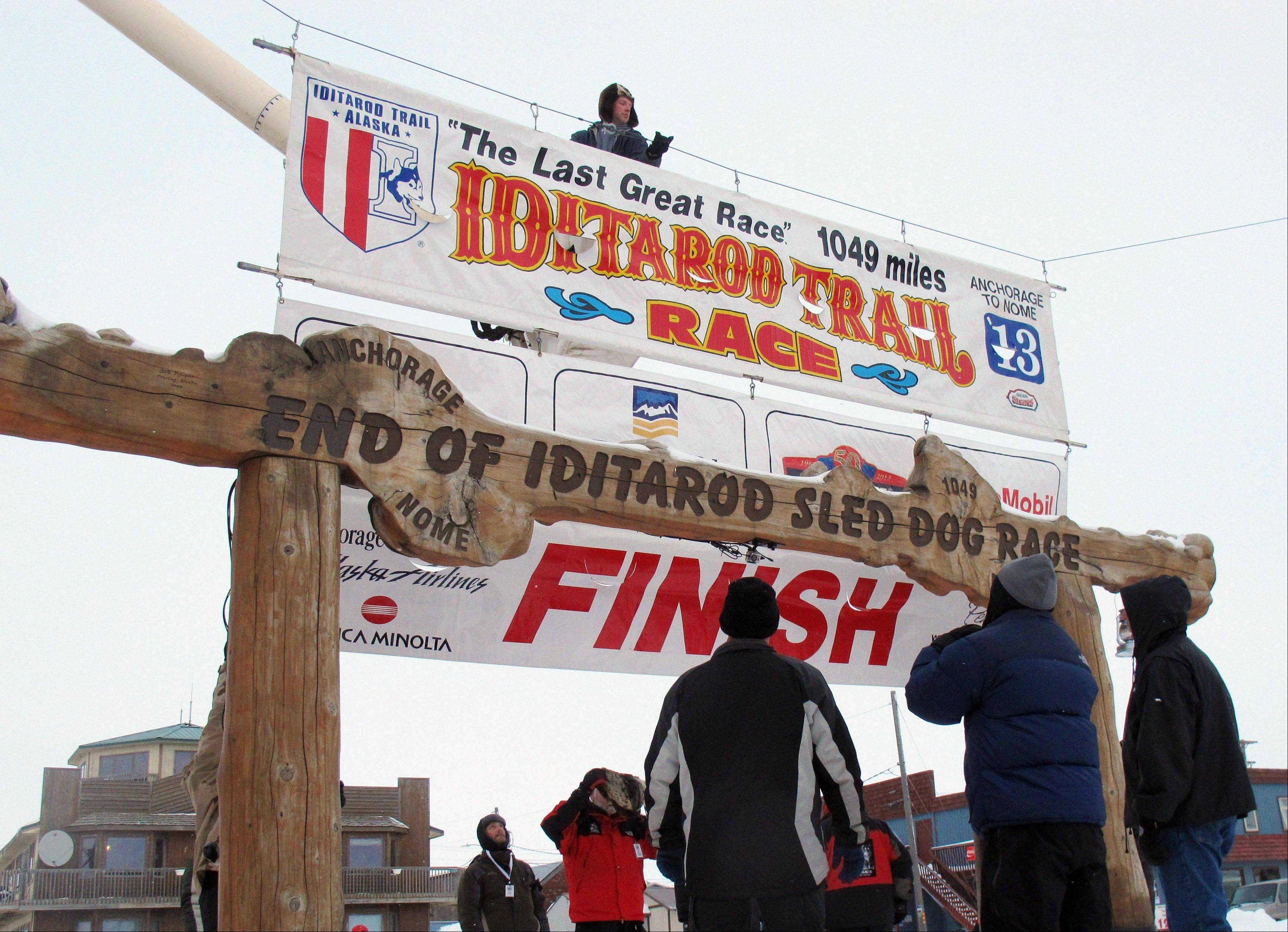 Volunteers hang a banner above the burled arch, which serves as the finish line for the 1,000-mile Iditarod Trail Sled Dog Race in Nome, Alaska.