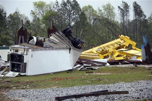 Wind twisted lifts and cranes and a trailer are among the debris that litter the grounds of Contract Fabricators Inc. in Kemper County, where authorities said one person died and another was injured when an apparent tornado hit Thursday, April 11, 2013 near De Kalb, Miss. Bent pieces of tin hung from the heavily damaged building and a tractor trailer was twisted and overturned. Debris from the business was strewn through the woods across the street. Sightseers drove slowly by the destruction, taking pictures.