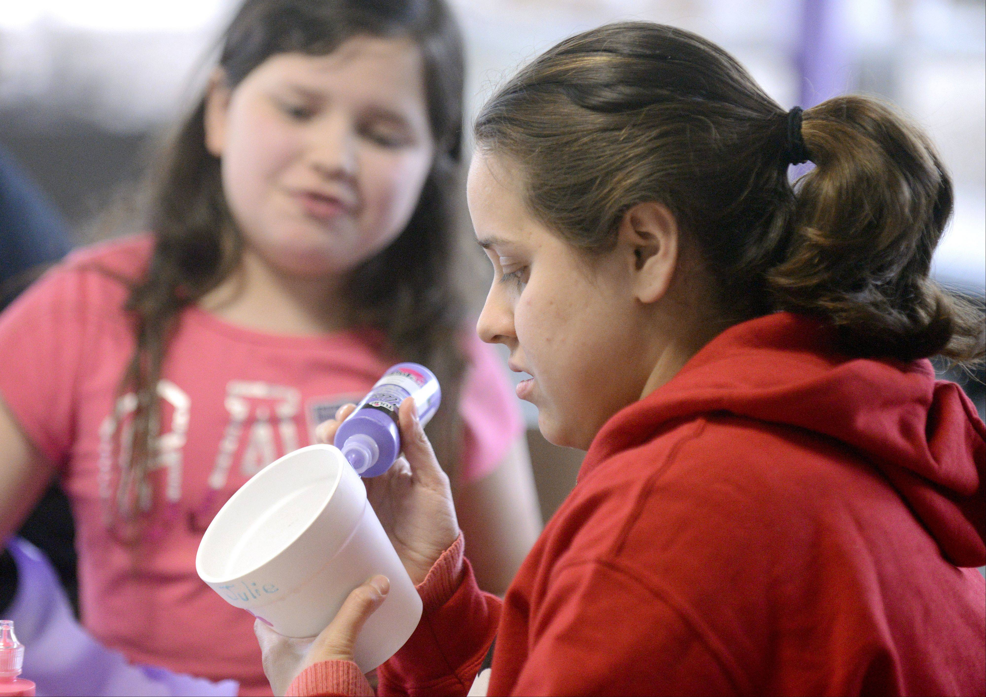 Vanessa Velasquez of Elgin decorates a flower pot with her little sister, Julissa, 10, at the American Cancer Society Relay For Life kickoff event Saturday at Elgin Community College. Velasquez is a student at the college, and she and Julissa will be participating in the June 14-15 event for the first time this year. They are walking to honor a family friend who was recently diagnosed with lung cancer.