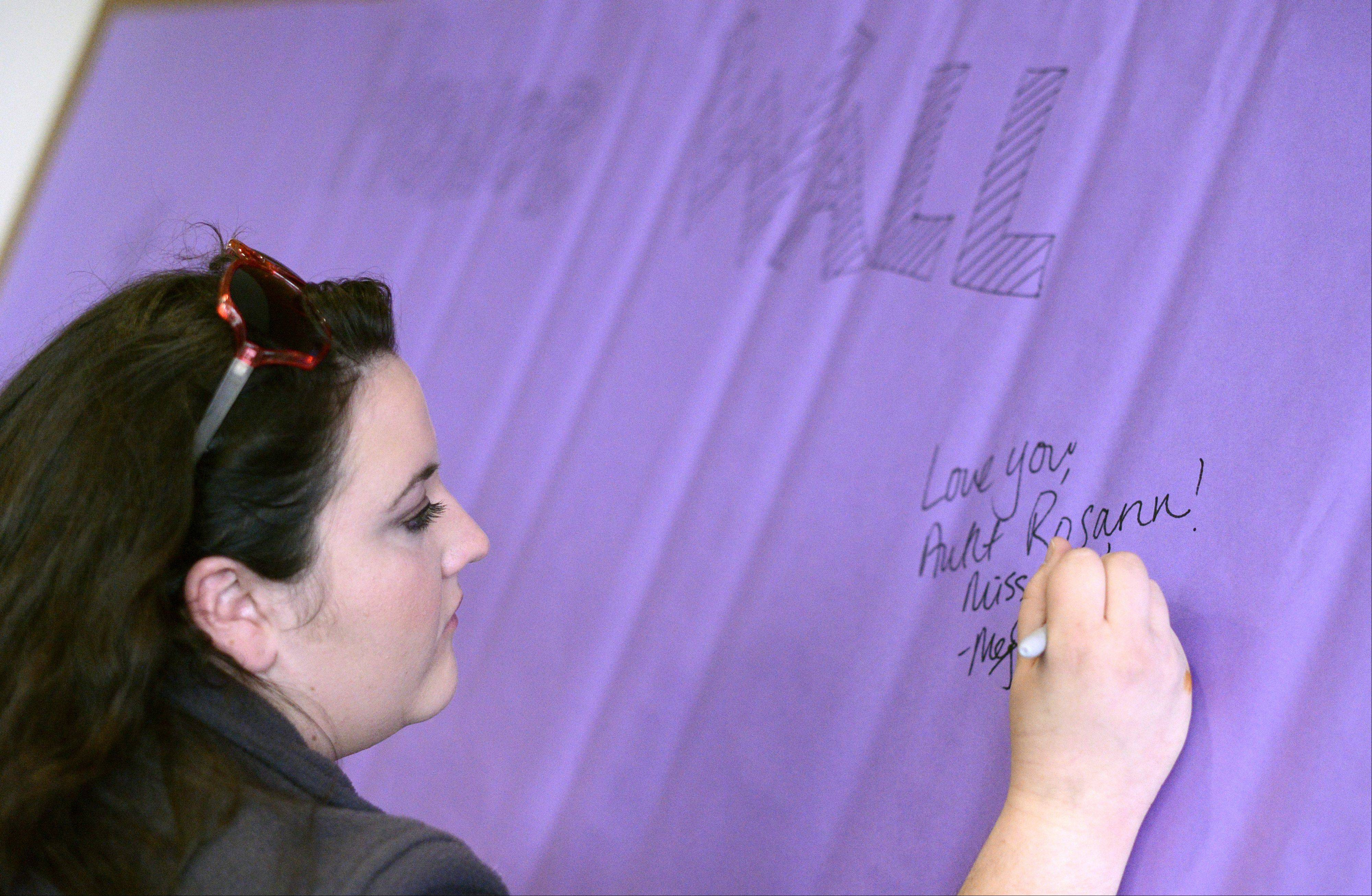 "Meghan Goldbeck, a field associate with the American Cancer Society, signs an ""honor wall"" banner to remember her great-aunt who died of breast cancer. Goldbeck and a few dozen people gathered at Elgin Community College to kick off the countdown to the ACS Relay For Life, to be held June 14-15."