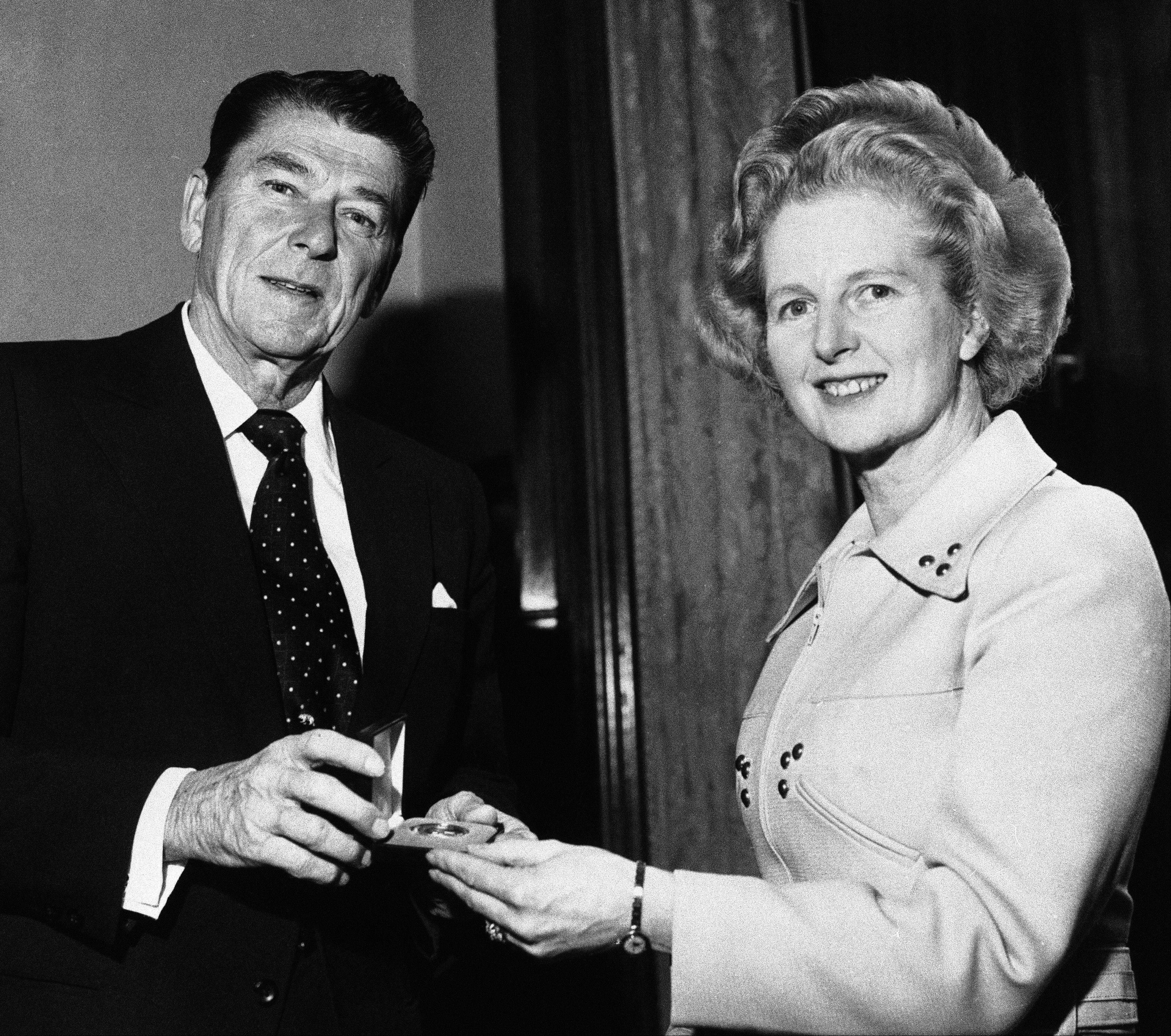 Former California Governor Ronald Reagan presents a silver dollar medallion to Opposition Leader Margaret Thatcher when he visited her office at the House of Commons in London.