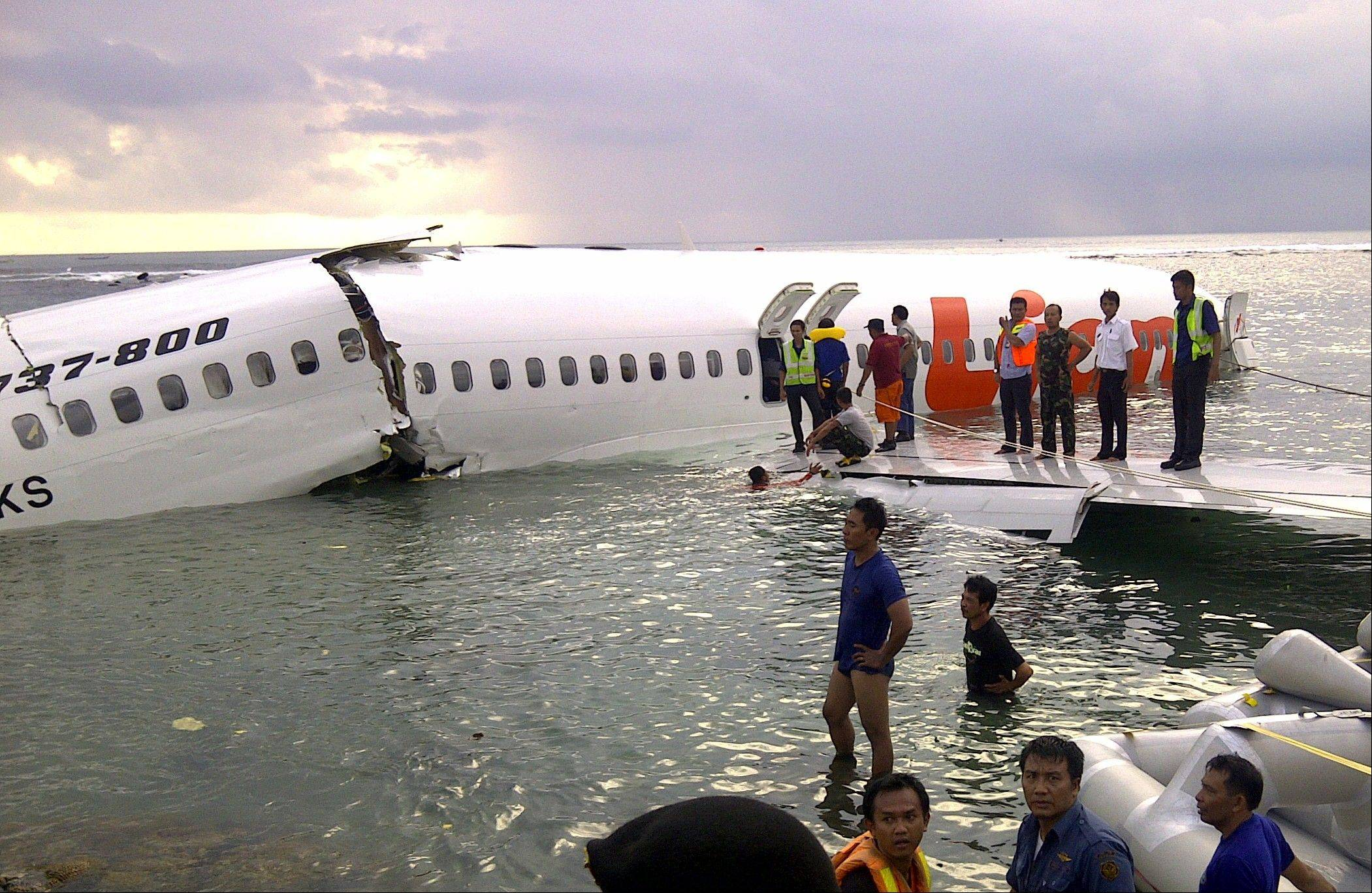 Rescuers stand near the wreckage Saturday of a crashed Lion Air plane in Bali, Indonesia.