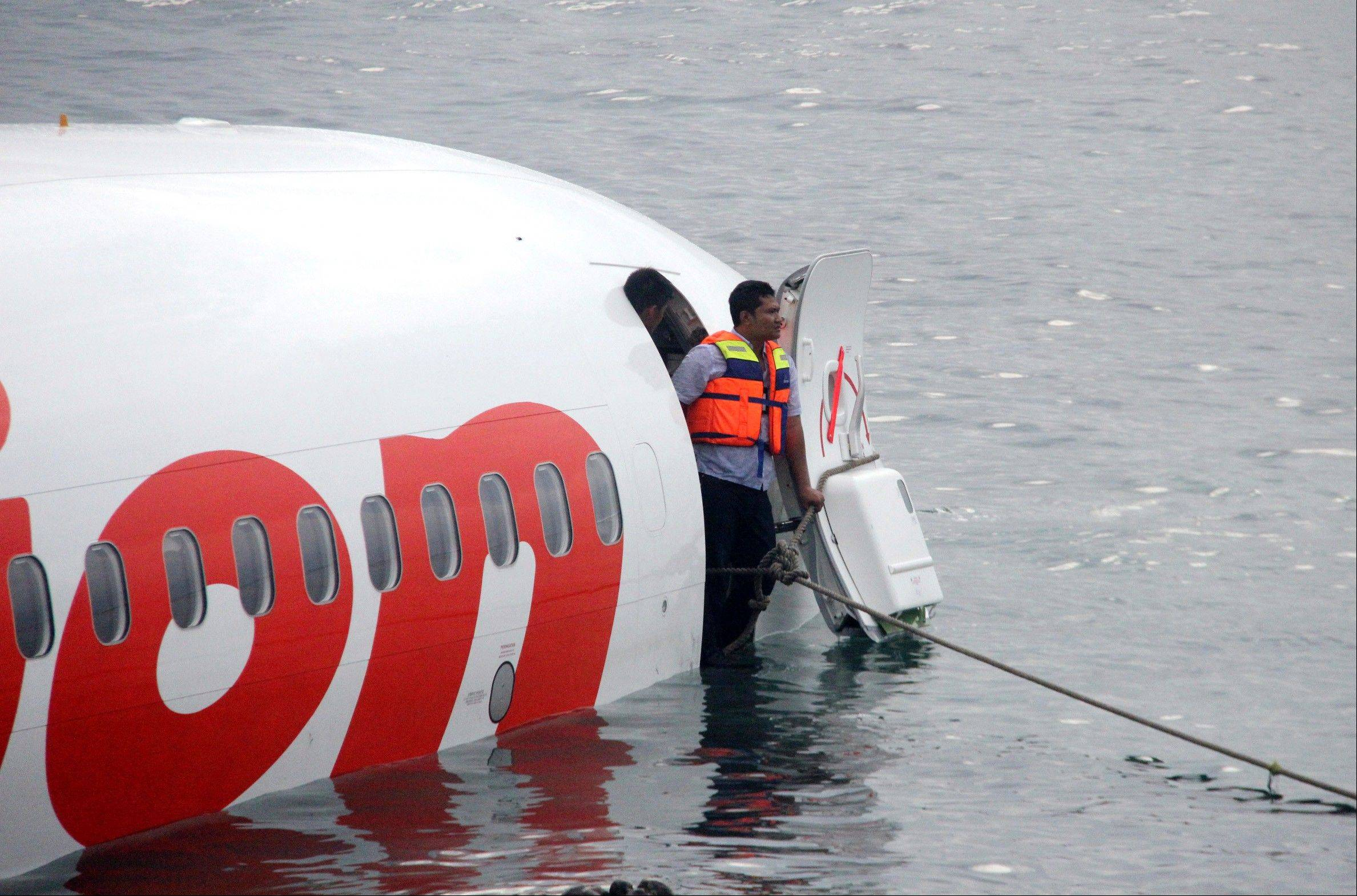 A rescue worker stands at the doorway of a crashed Lion Air plane on the water near the airport in Bali, Indonesia.