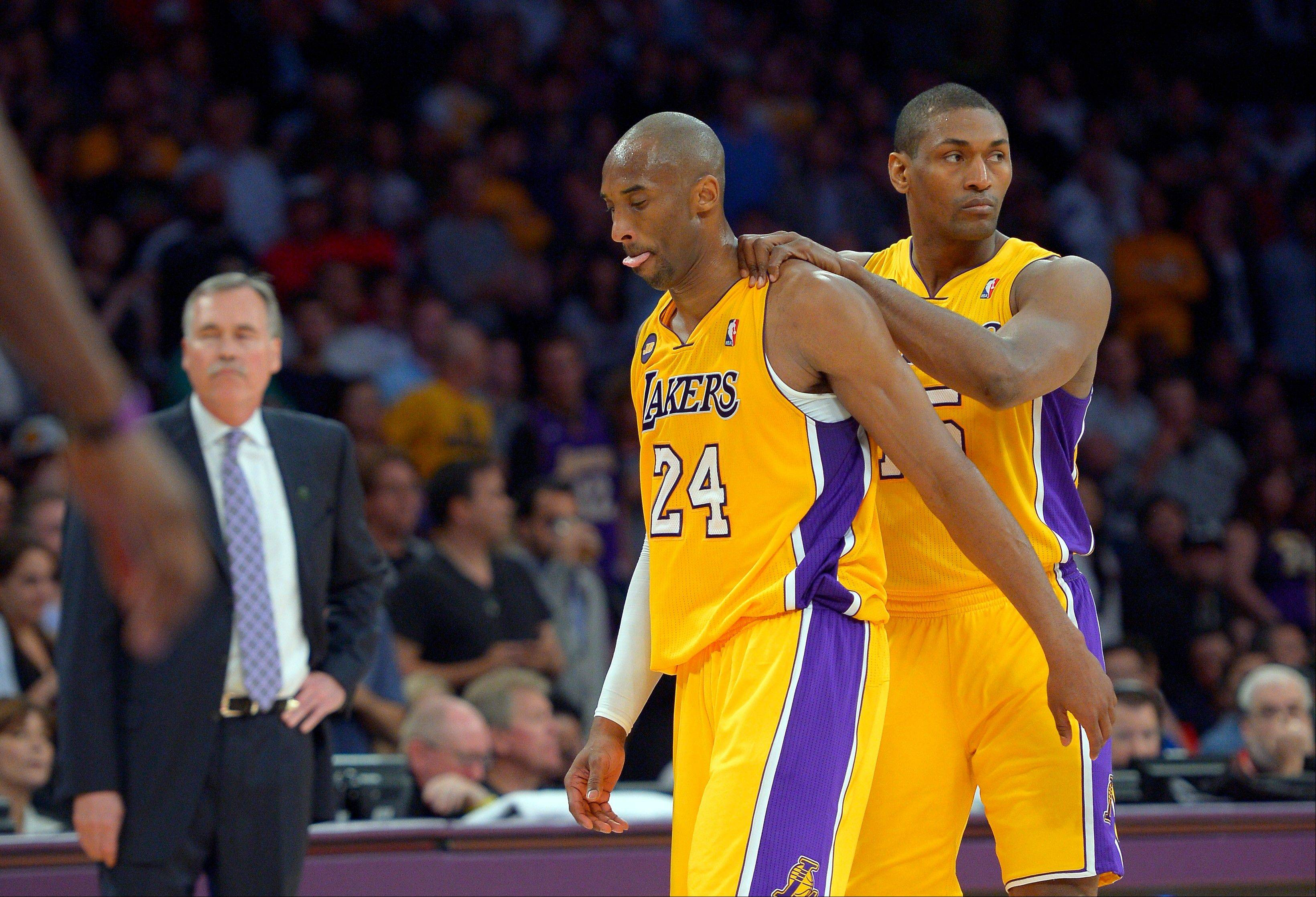 Los Angeles Lakers guard Kobe Bryant, center, is consoled by forward Metta World Peace, right, as head coach Mike D'Antoni looks on after being injured during the second half of their NBA basketball game against the Golden State Warriors, Friday, April 12, 2013, in Los Angeles. The Lakers won 118-116.