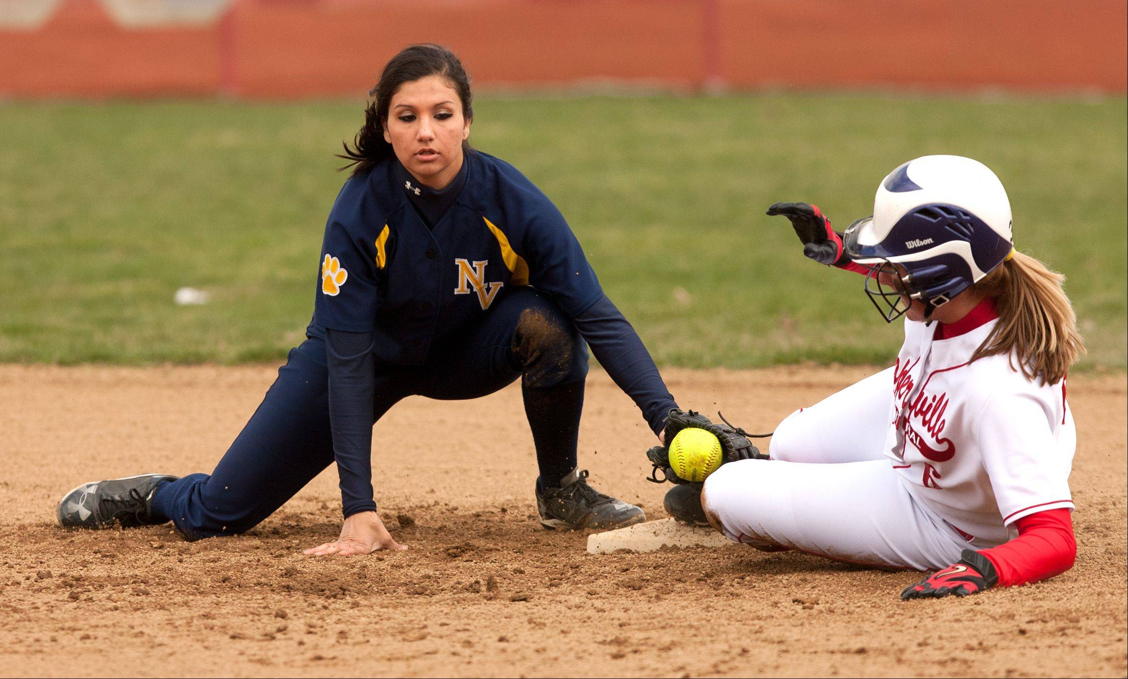 Naperville Central's Megan Nerger slides safely under the tag of Neuqua Valley's Jamie O'Brien on Saturday at Naperville Central.
