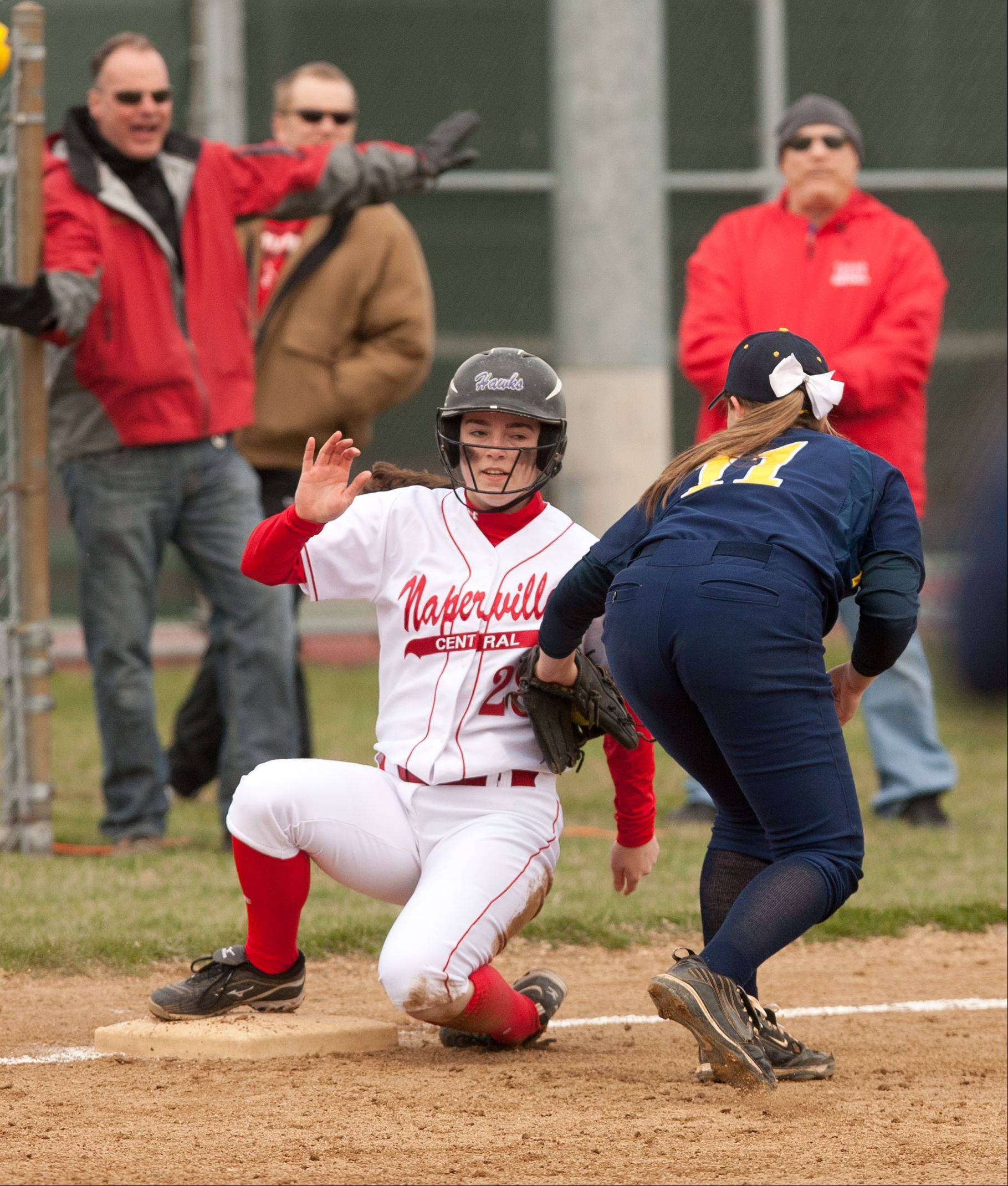 Naperville Central's Lisa Tassi slides safely into third base under the tag of Neuqua Valley's Alyssa Mazurek on Saturday at Naperville Central.