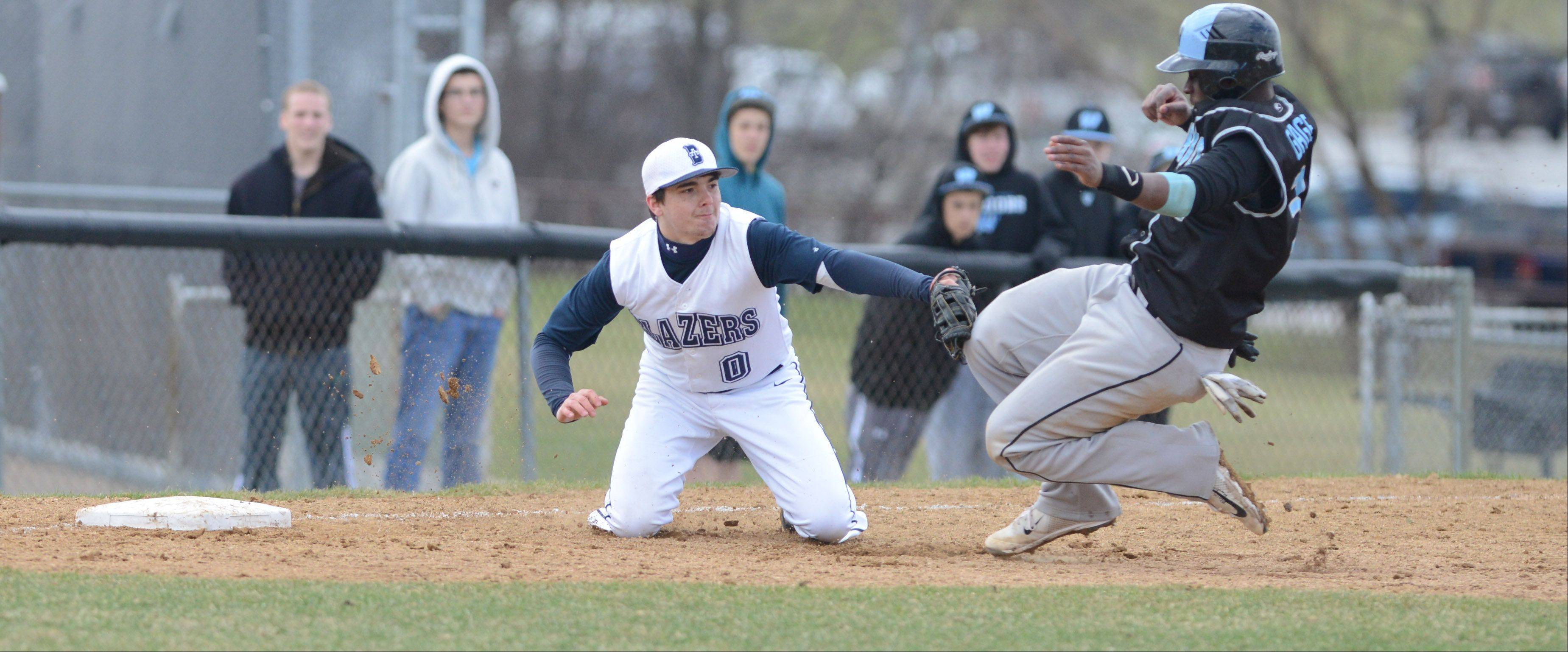 Brad Schonder of Addison Trail just misses the tag on Gabe Gage of Willowbrook at third base on Saturday in Addison.