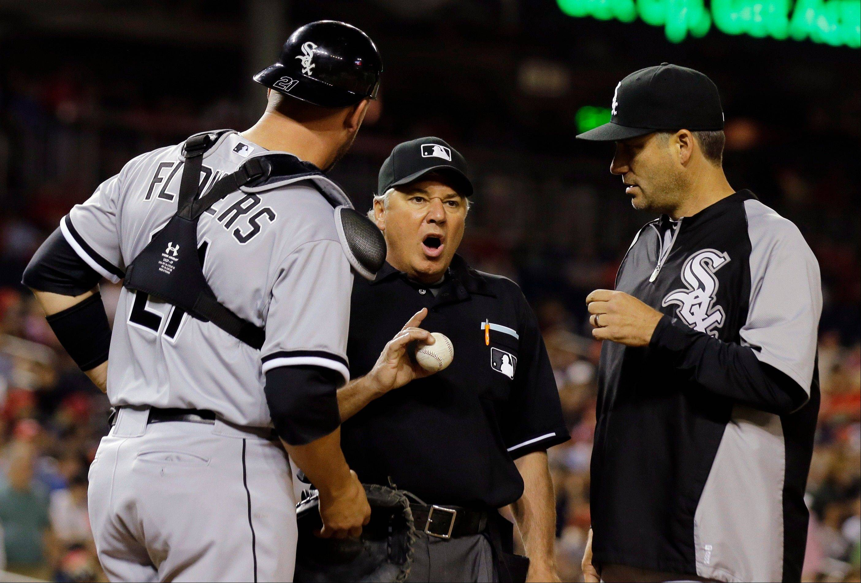 Tyler Flowers (21) and manager Robin Ventura talk with home plate umpire Tom Hallion about a past ball call that scored a run during the fourth inning of an interleague baseball game against the Chicago White Sox at Nationals Park, Thursday, April 11, 2013, in Washington.