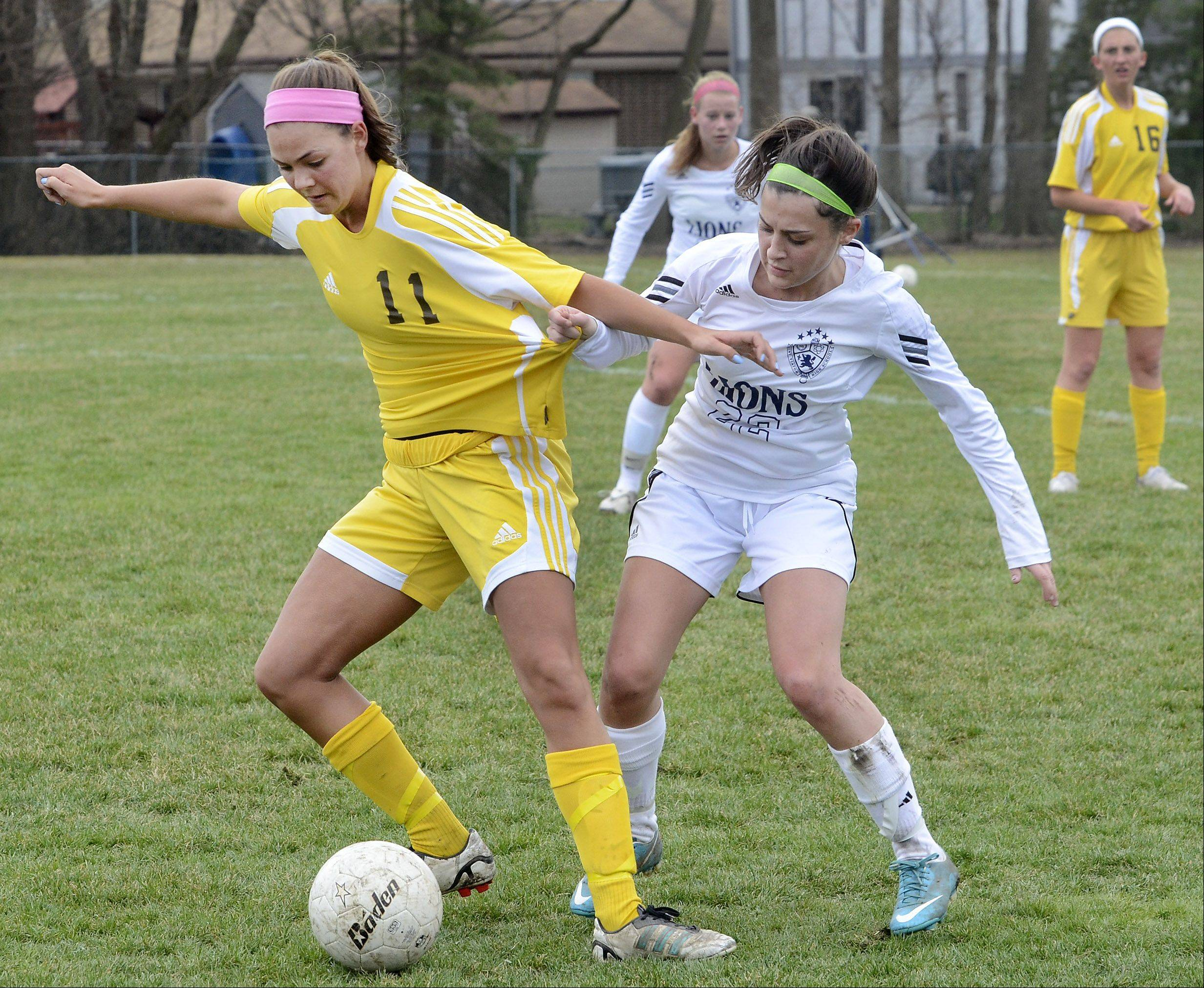St. Viator's Maria Petrillo, right, grabs hold of the jersey of Carmel's Annie DiVenere on Saturday in Arlington Heights.