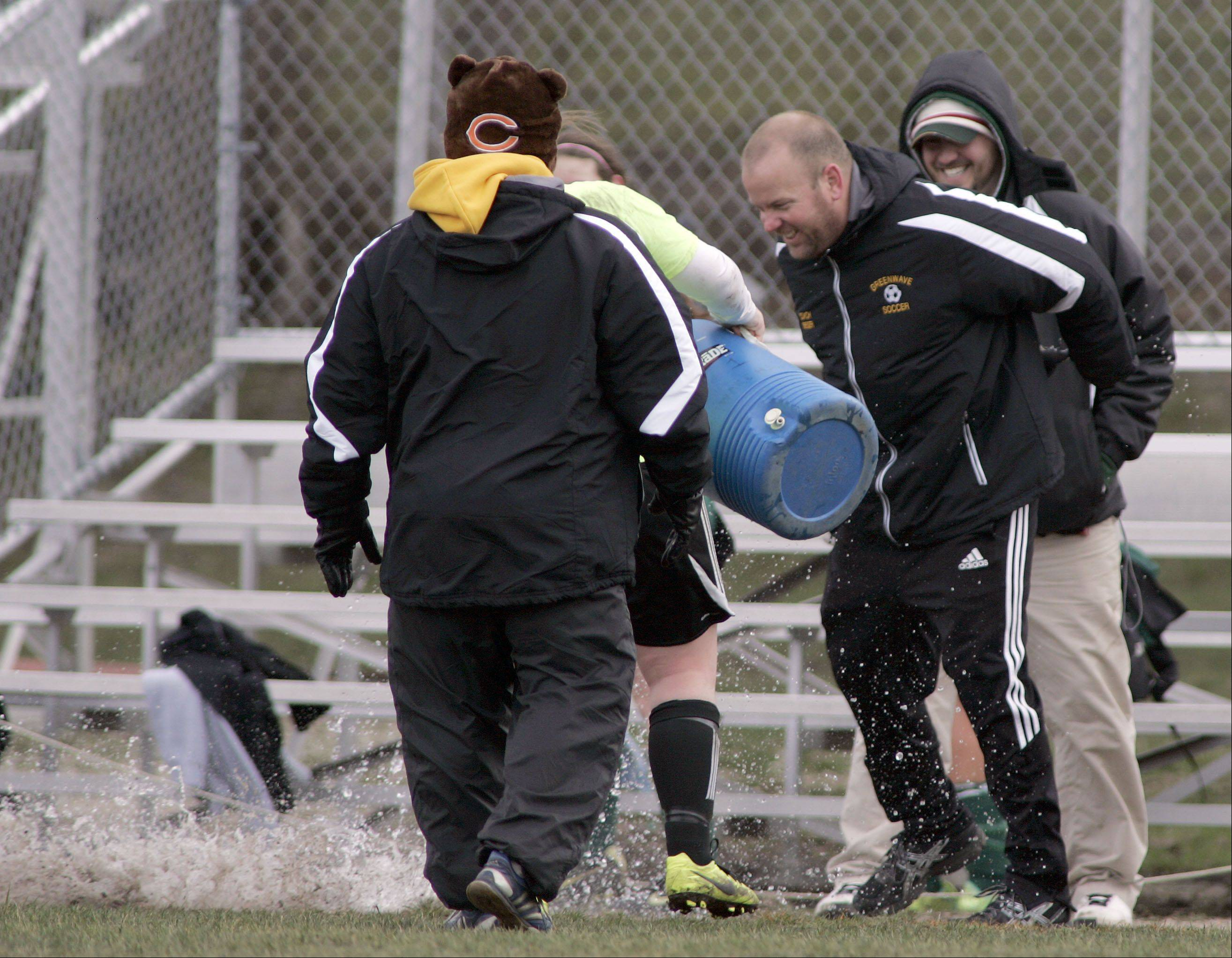 St. Edward soccer coach Tim Brieger barely sidesteps a full water bucket after his 200th win with the girls program.