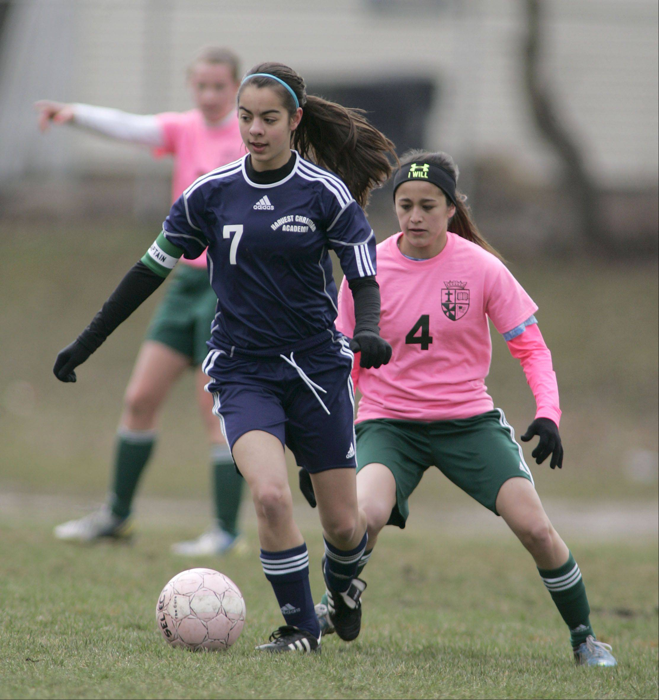 Harvest Christian's Brittany Salazar (7) finds her way around St. Edward's Monica Ramirez during girls soccer in Elgin Saturday.