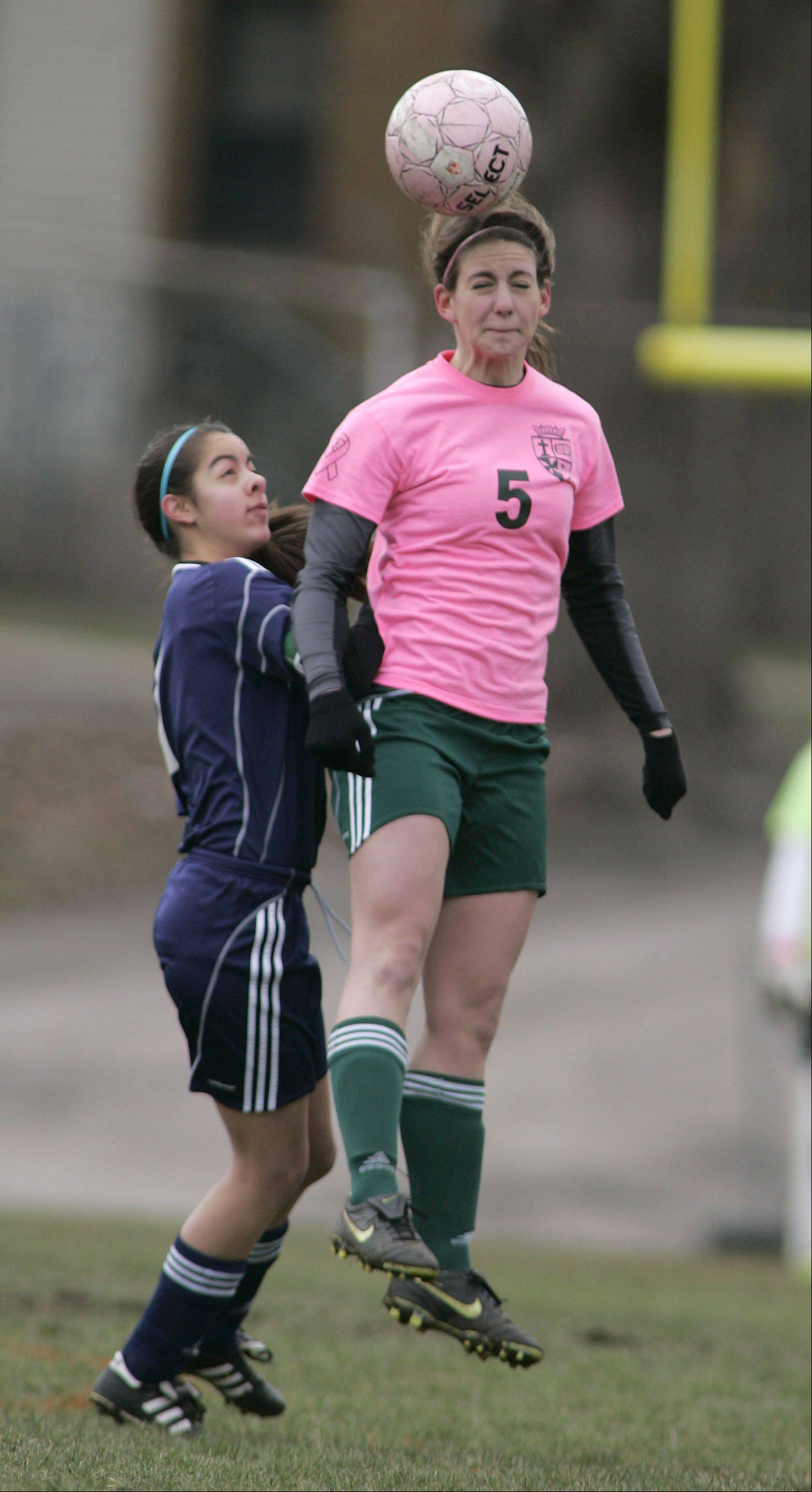 Harvest Christian's Brittany Salazar (7) goes head to head with St. Edward's Rena Ranallo during girls soccer in Elgin Saturday.