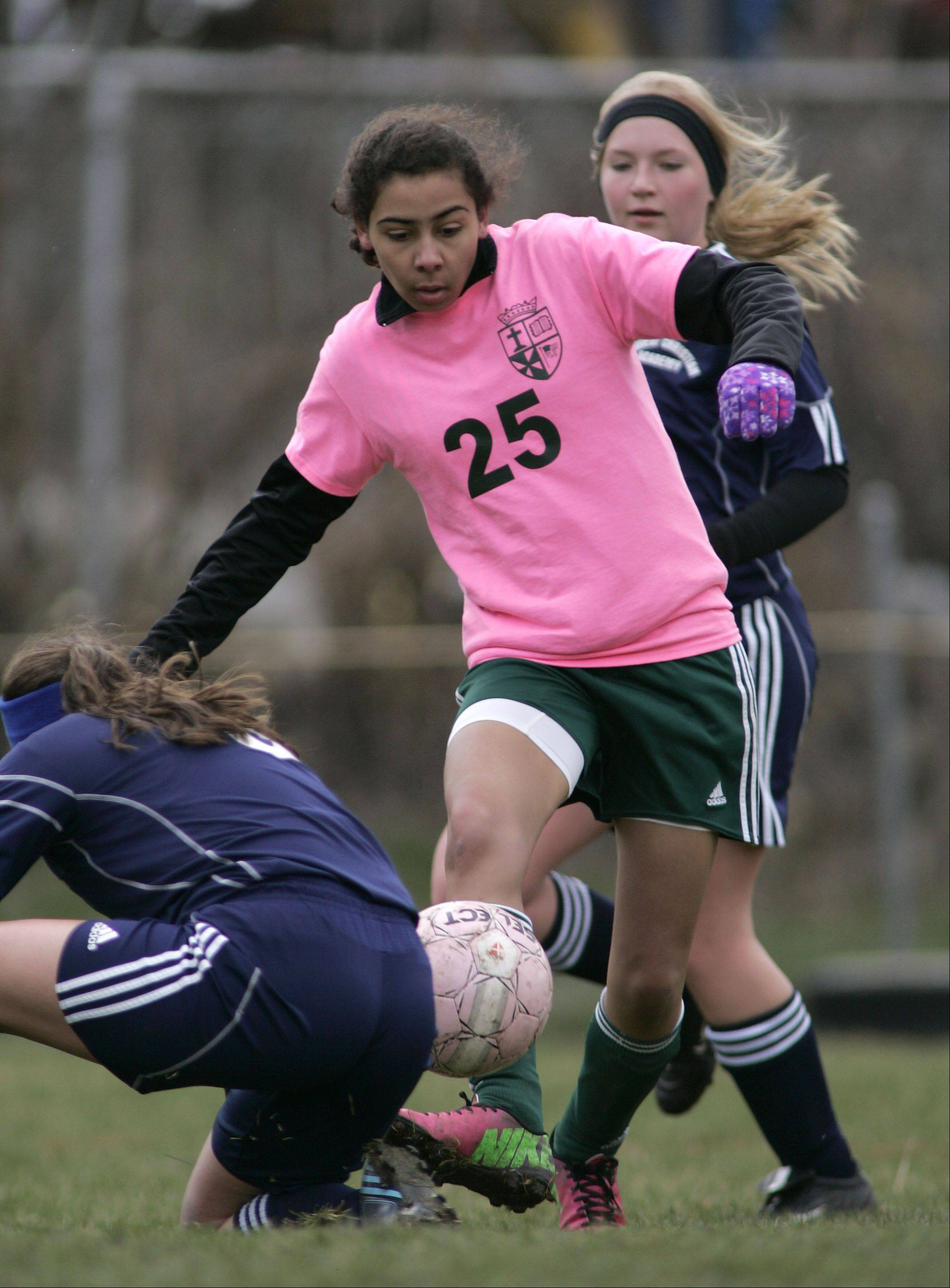 St. Edward's Theresa McFadden (25) weaves her way between two Harvest Christian girls during soccer in Elgin Saturday.