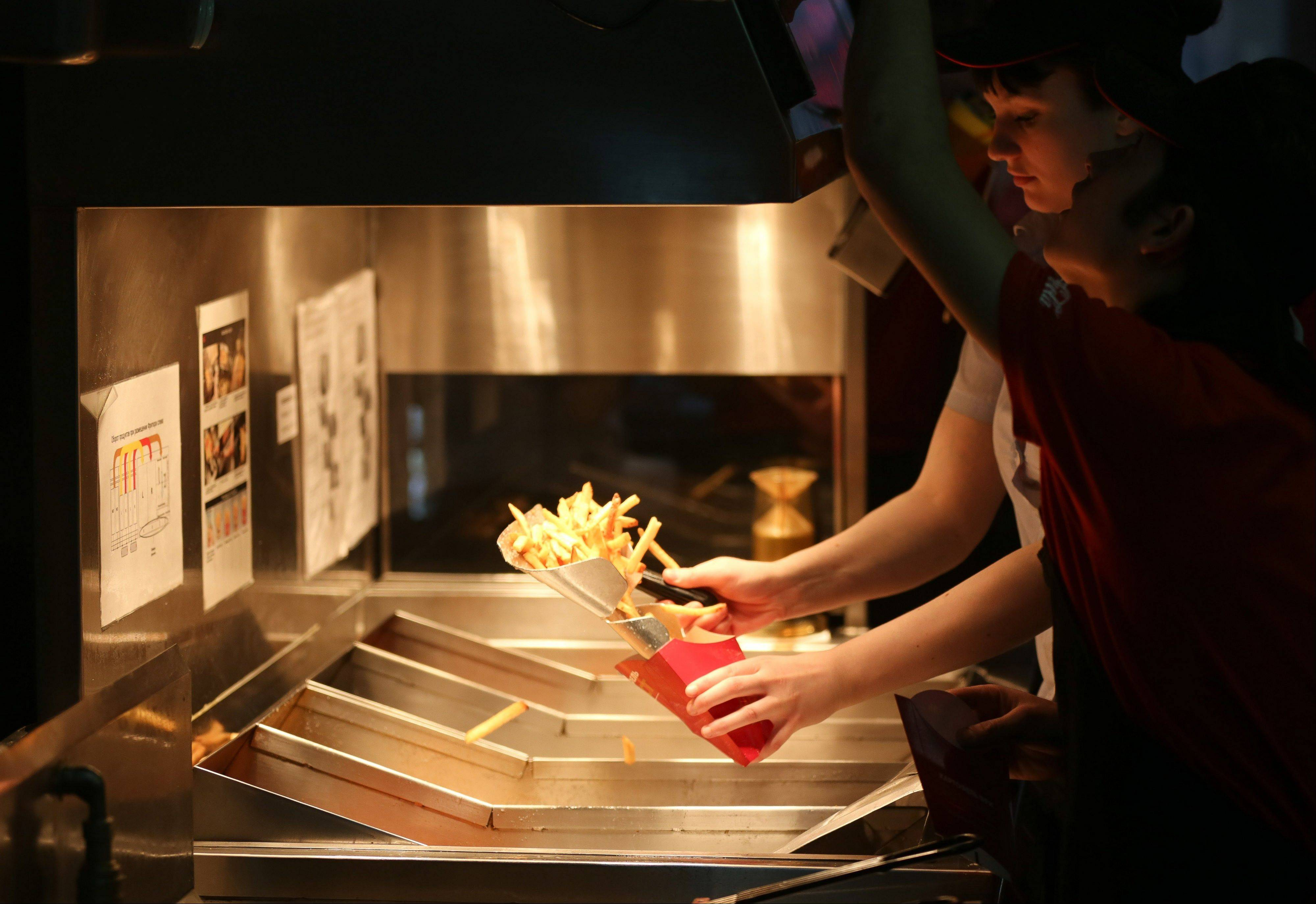 An employee prepares a portion of french fries for a customer in the kitchen area of a Wendy�s fast food restaurant in Moscow, Russia.