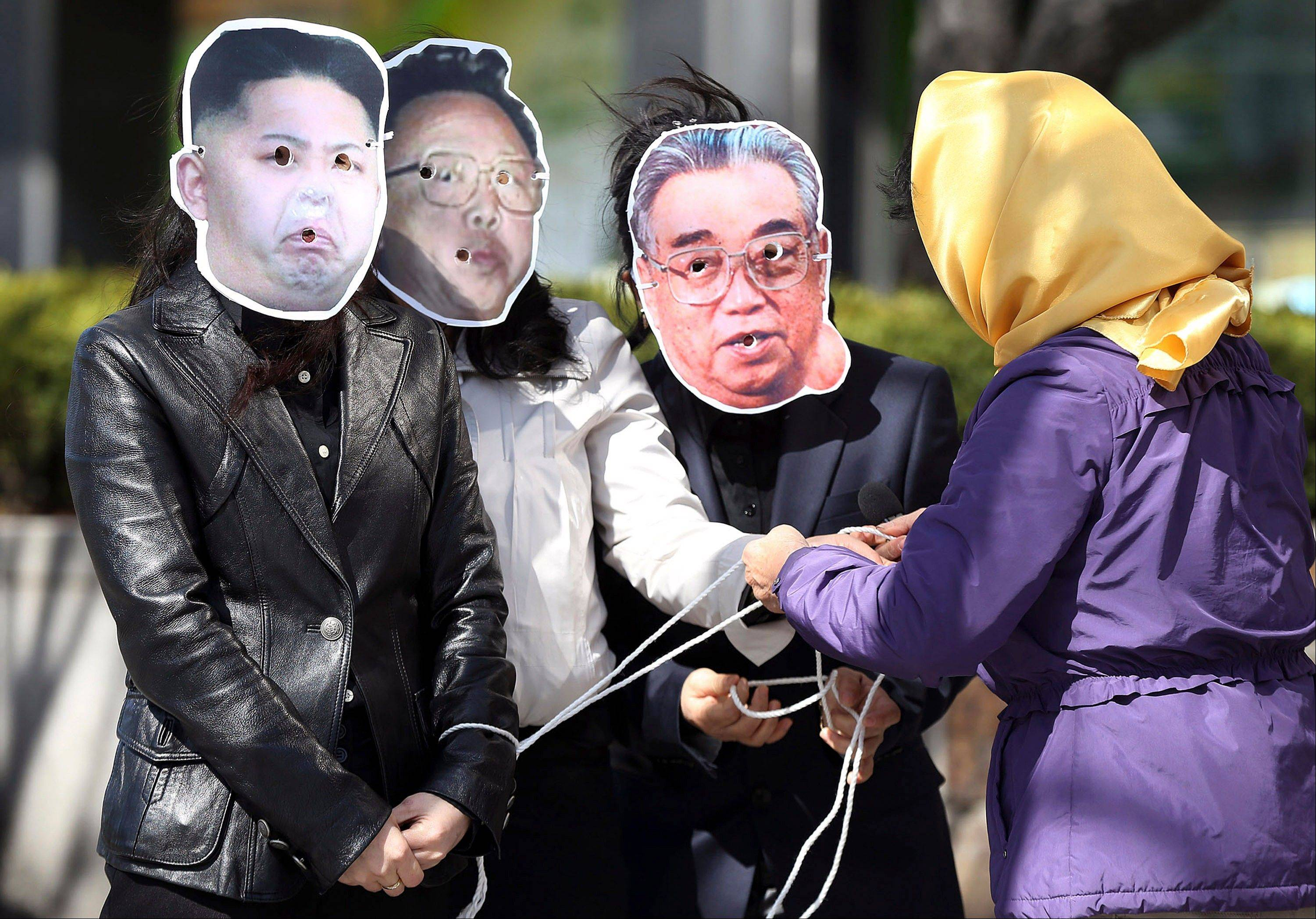 A North Korean defector ties hands of South Korean activists wearing masks of North Korean leader Kim Jong Un, left, late North Korean leader Kim Jong Il, center, and Kim Il Sung, the late founder of North Korea, with ropes during a rally against North Korea on the eve of 101st anniversary of founder Kim�s birthday, in Seoul, South Korea, Sunday.