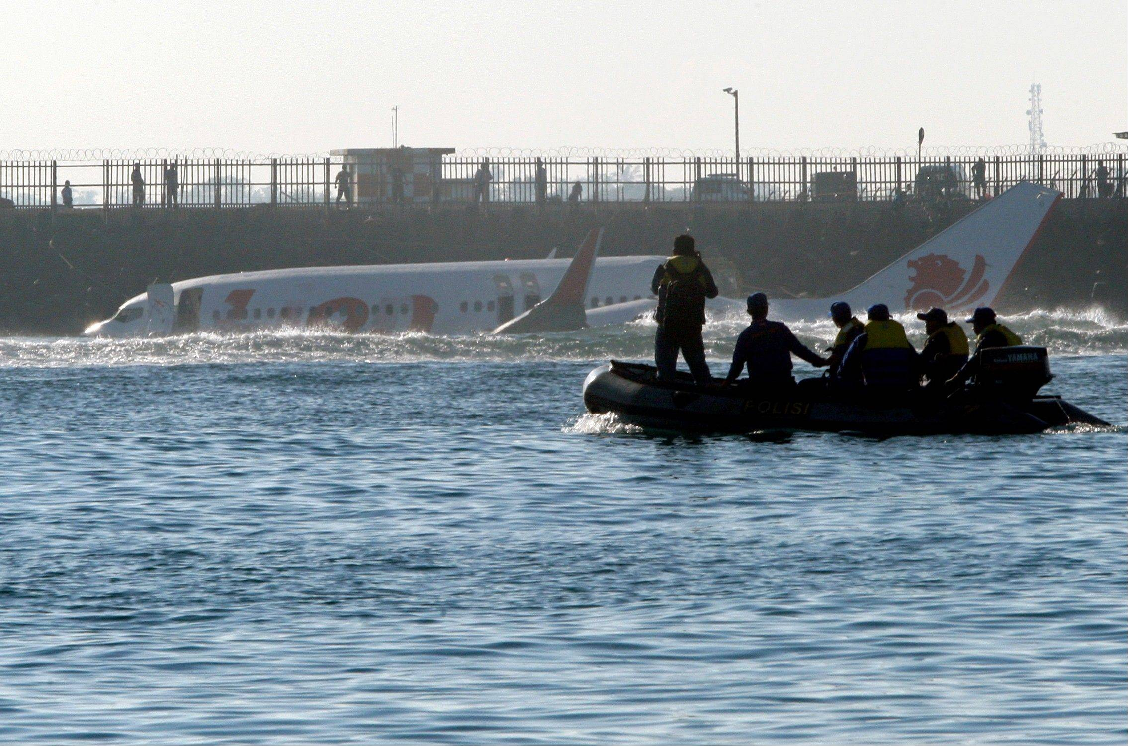 Indonesian marine police look at the wreckage of a Lion Air jet following Saturday's crash near the airport in Bali, Indonesia on Sunday. All 108 passengers and crew survived after the new Lion Air jet crashed into the ocean and snapped into two while attempting to land Saturday on the Indonesian resort island of Bali, injuring up to 45 people.