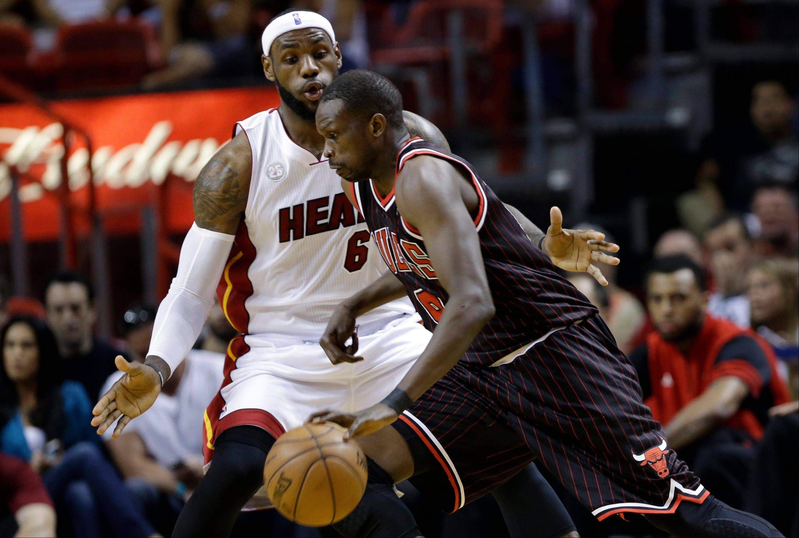 The Bulls' Luol Deng drives to the basket against the Heat's LeBron James on Sunday.