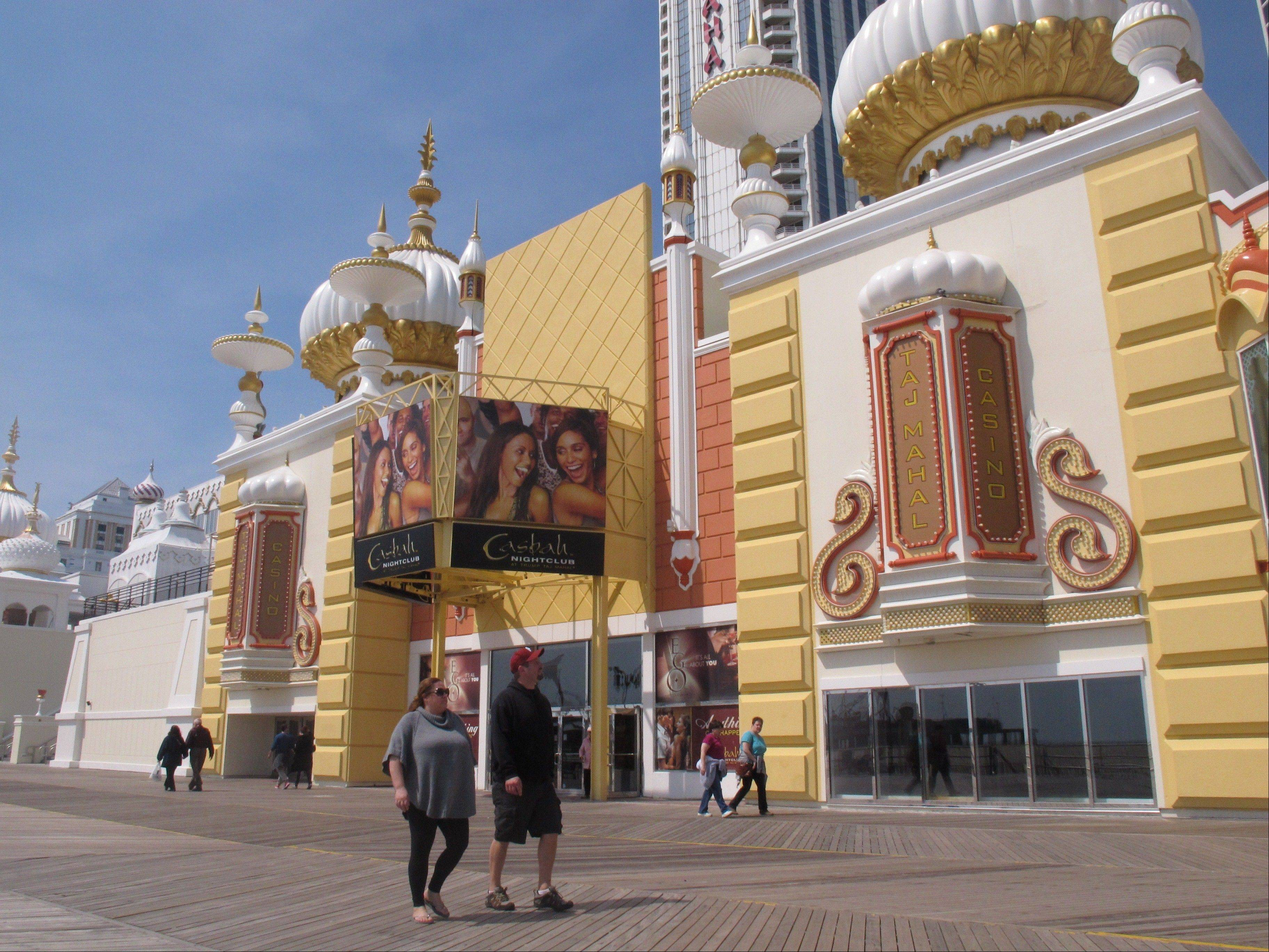 Pedestrians on the Atlantic City N.J. boardwalk look up at the newly renovated facade of the Trump Taj Mahal Casino Resort. Atlantic City tourism officials have unveiled a new $20 million advertising campaign.