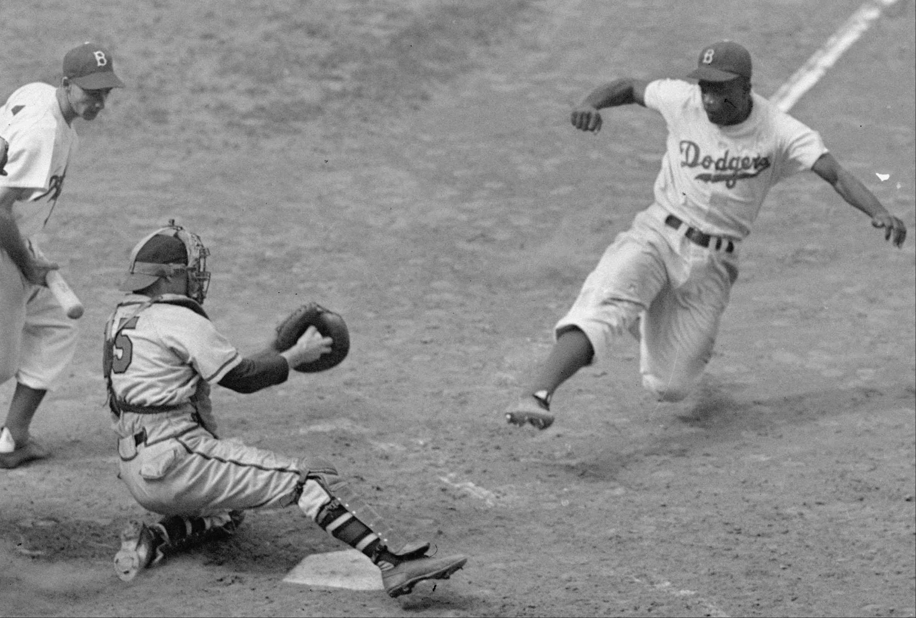 A 1948 file photo shows Brooklyn Dodgers Jackie Robinson, right, stealing home plate as Boston Braves' catcher Bill Salkeld is thrown off-balance on the throw during the fifth inning at Ebbets Field in New York.