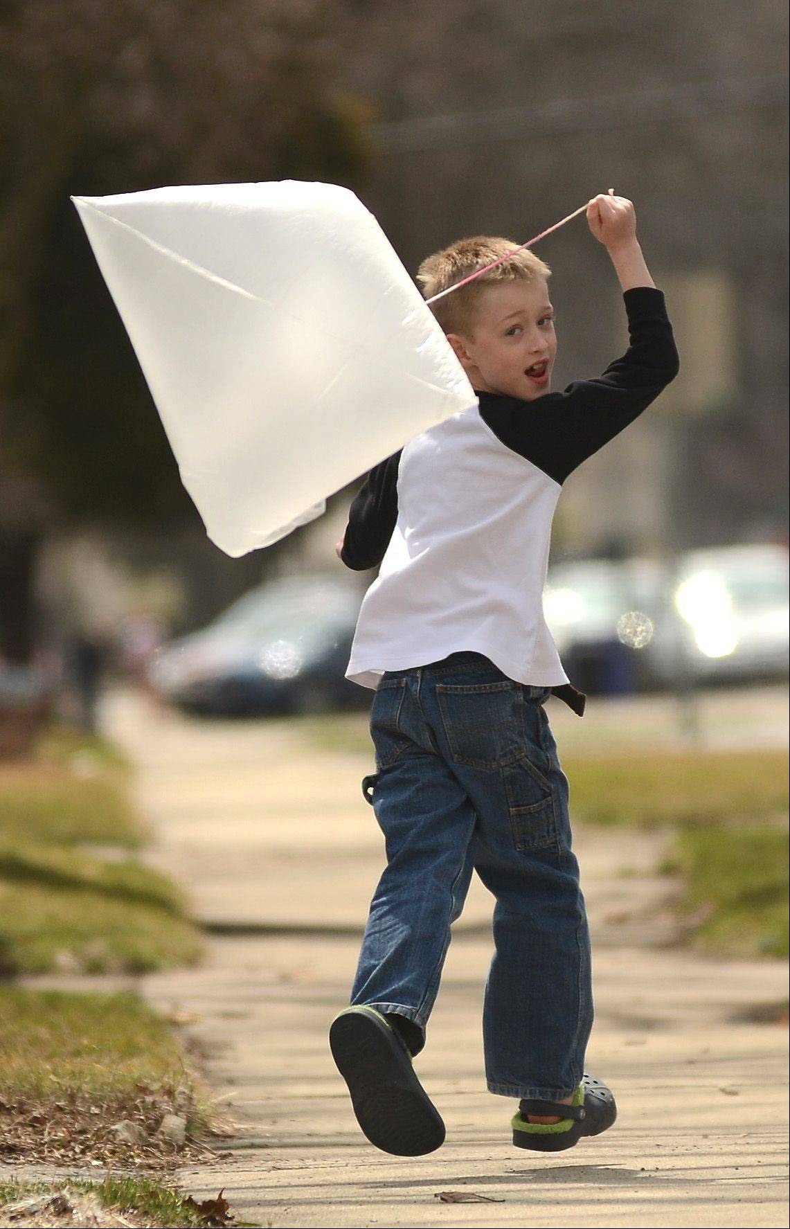 Owen Williams, 7, flies a homemade kite made from a plastic bag in front of his Wheaton home Monday.