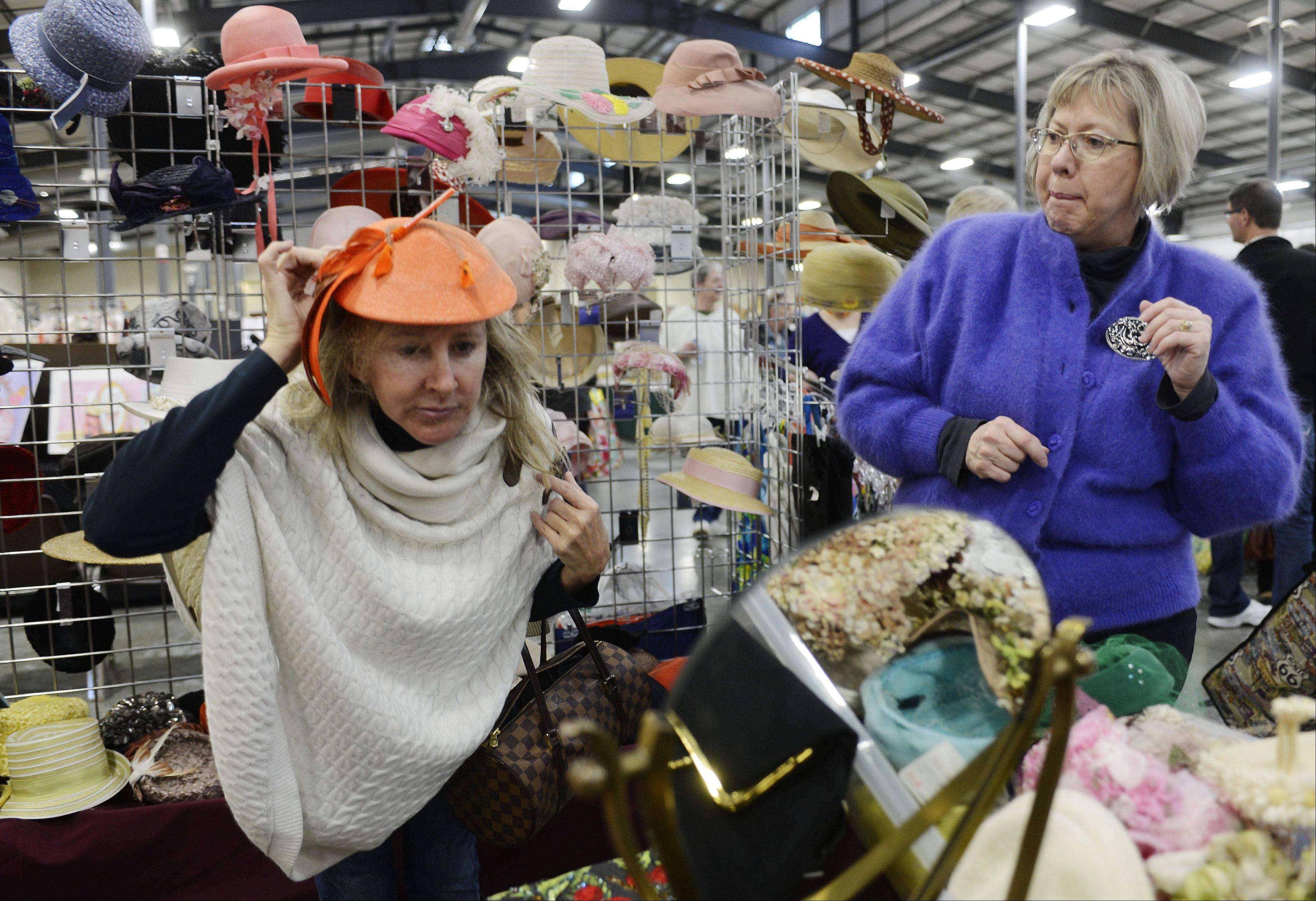 Maura Shackleton Schuster of Lake Forest, left, tries on a Gimble Brothers pork pie hat with the assistance of dealer Cindy Budde of Milwaukee during the Antiques and Collectible Flea Market at the Lake County Fairgrounds in Grayslake Saturday.