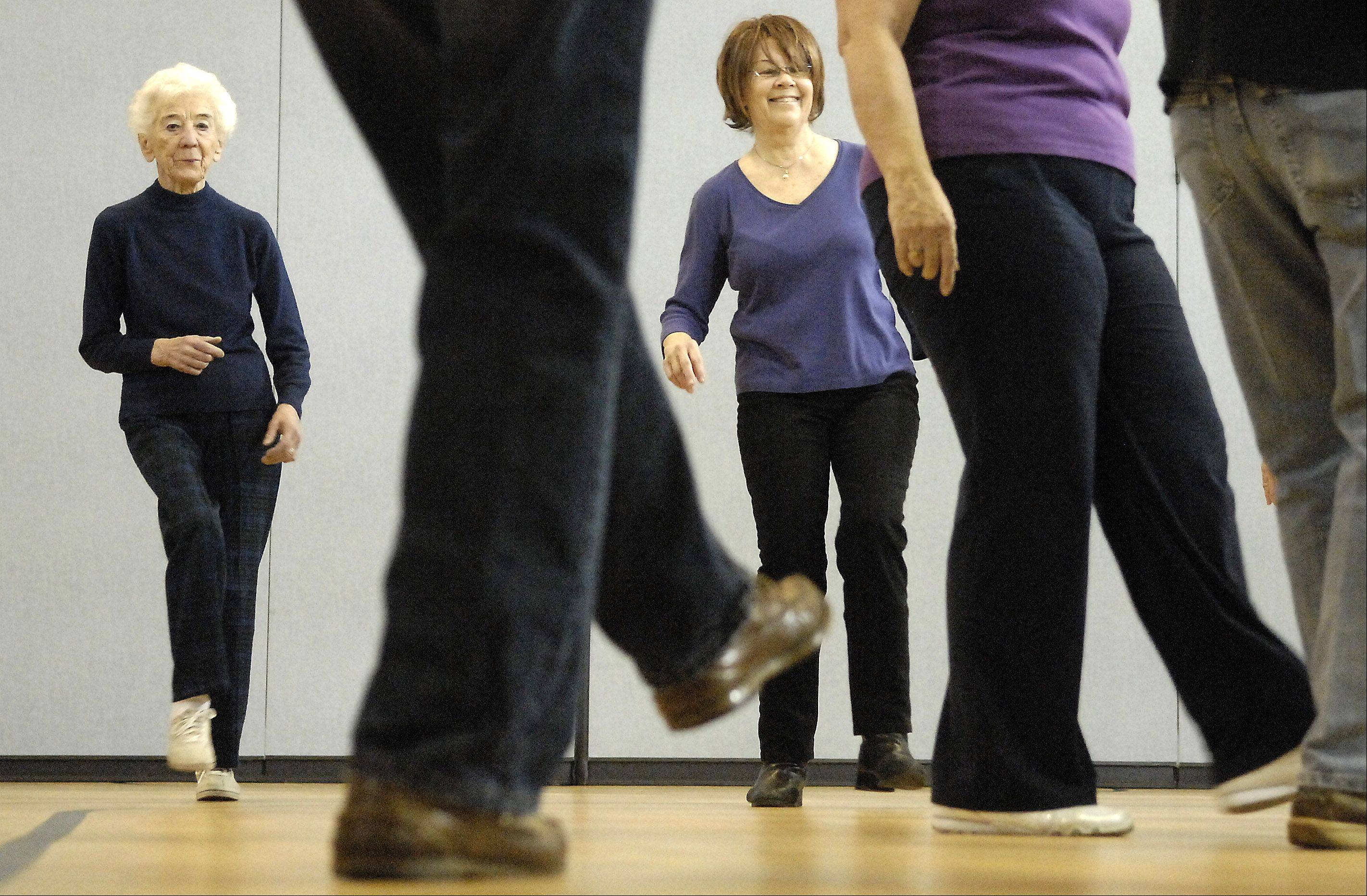 Alena Stybr, left, of St. Charles and Judy Amesbury, of Geneva, get their kicks during a line dance class at the Salvation Army in St. Charles Monday.