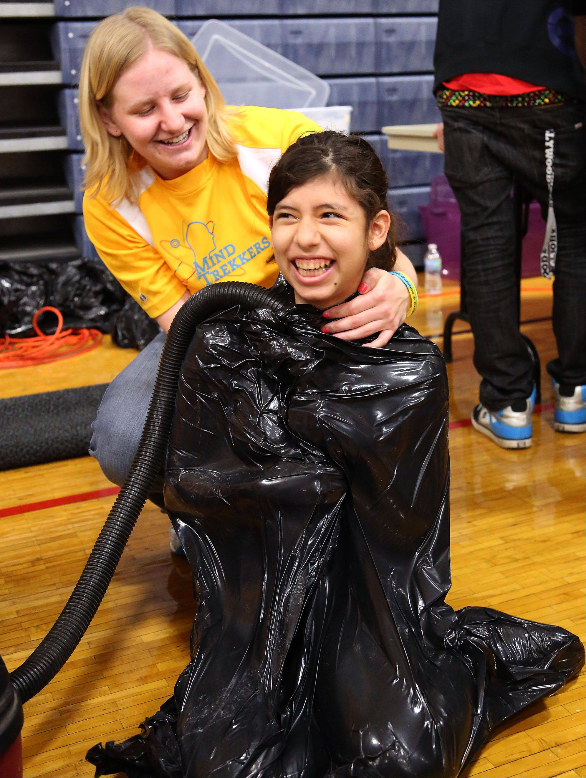 Casandra Ronning of Park West School in Round Lake is vaccum sealed into a garbage bag by Michigan Tech student Olivia Zajac during a science fair called Mind Trekkers led by the students and faculty of Michigan Tech University at the College of Lake County Friday.