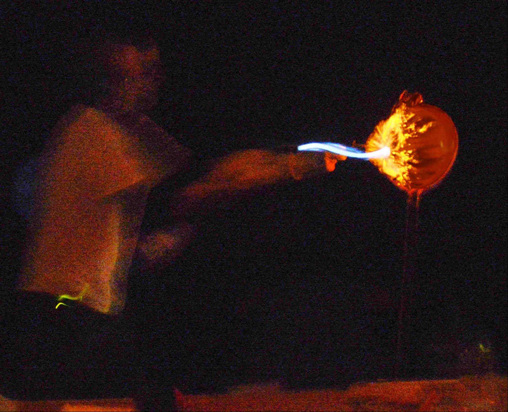 A hydrogen-filled balloon explodes in an instant as former Naperville North High School science teacher Lee Marek ignites it in a dark auditorium at Fermi Lab in Batavia Sunday during a Weird Science presentation.